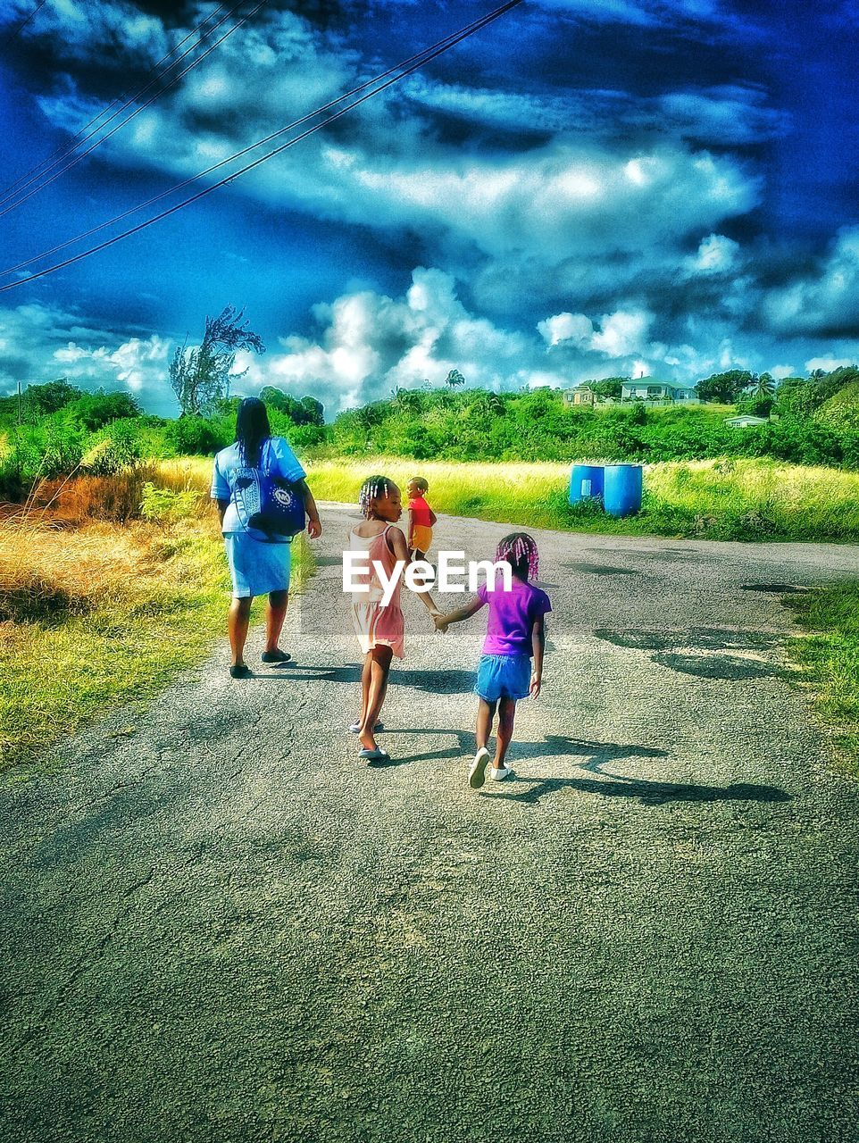 walking, girls, childhood, leisure activity, field, grass, full length, togetherness, real people, sky, boys, nature, day, rear view, casual clothing, running, lifestyles, outdoors, cloud - sky, bonding, growth, tree, landscape, men, women, child, rural scene, vacations, beauty in nature, friendship, adult, people