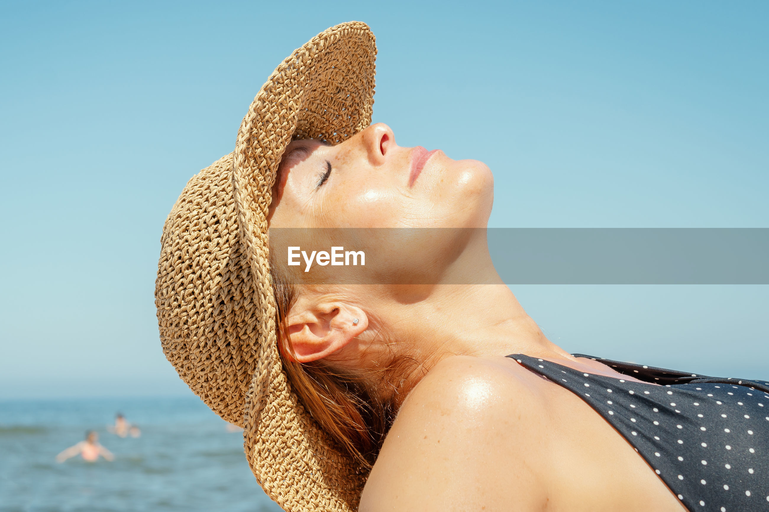 Close-up of woman in hat relaxing at beach