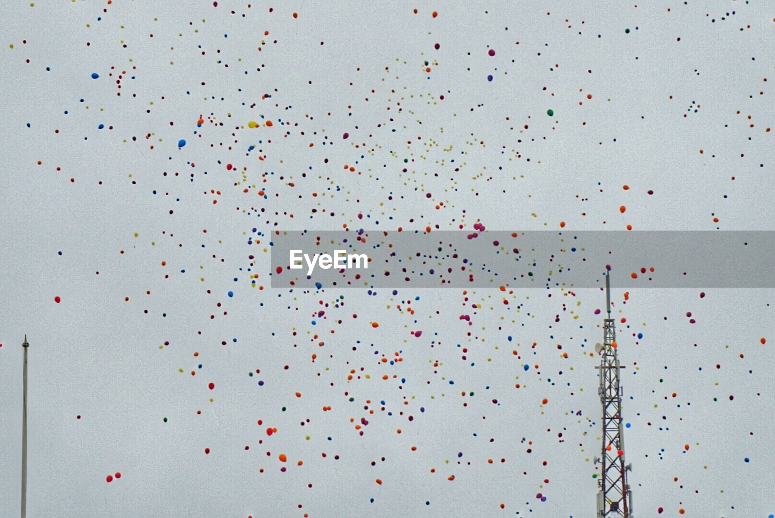 Low angle view of multi colored balloons flying by communications tower against sky