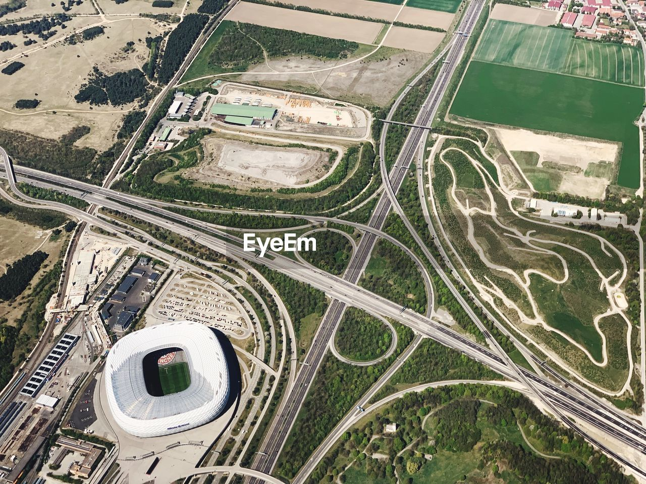 aerial view, road, transportation, high angle view, mode of transportation, built structure, no people, day, architecture, city, environment, outdoors, air vehicle, airplane, landscape, nature, flying, street, travel, motor vehicle, overpass, complexity, multiple lane highway