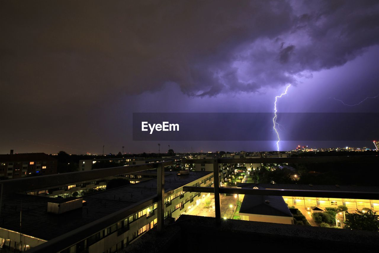 cloud - sky, lightning, storm, power in nature, thunderstorm, sky, night, architecture, illuminated, power, built structure, building exterior, storm cloud, forked lightning, beauty in nature, nature, warning sign, no people, city, outdoors, cityscape, purple, ominous