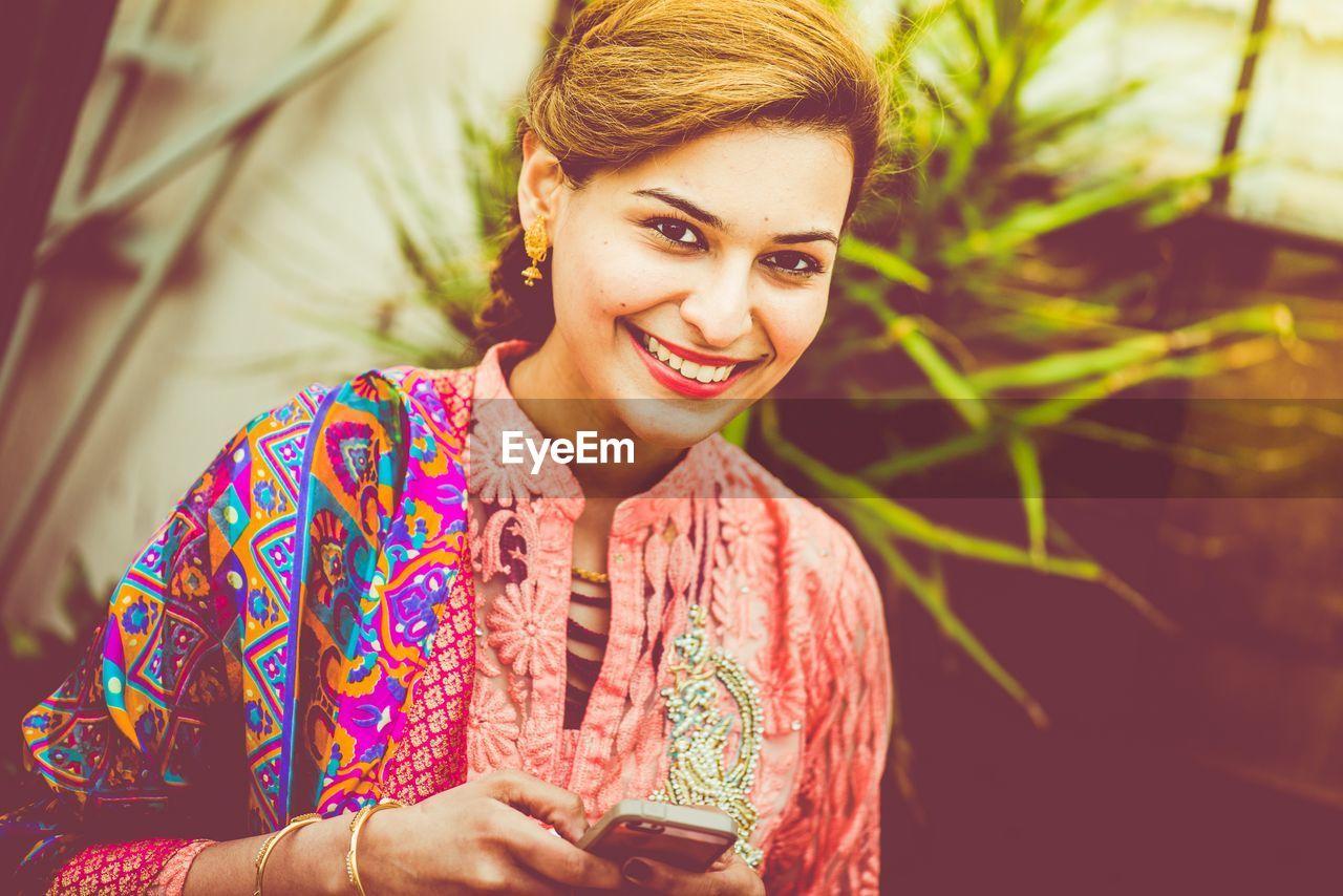 Portrait of happy beautiful woman using phone