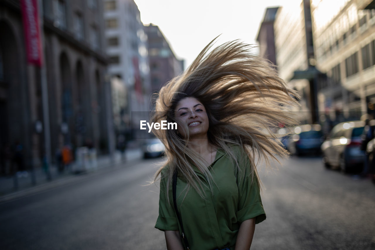 Portrait Of Young Woman Tossing Hair While Standing On City Street