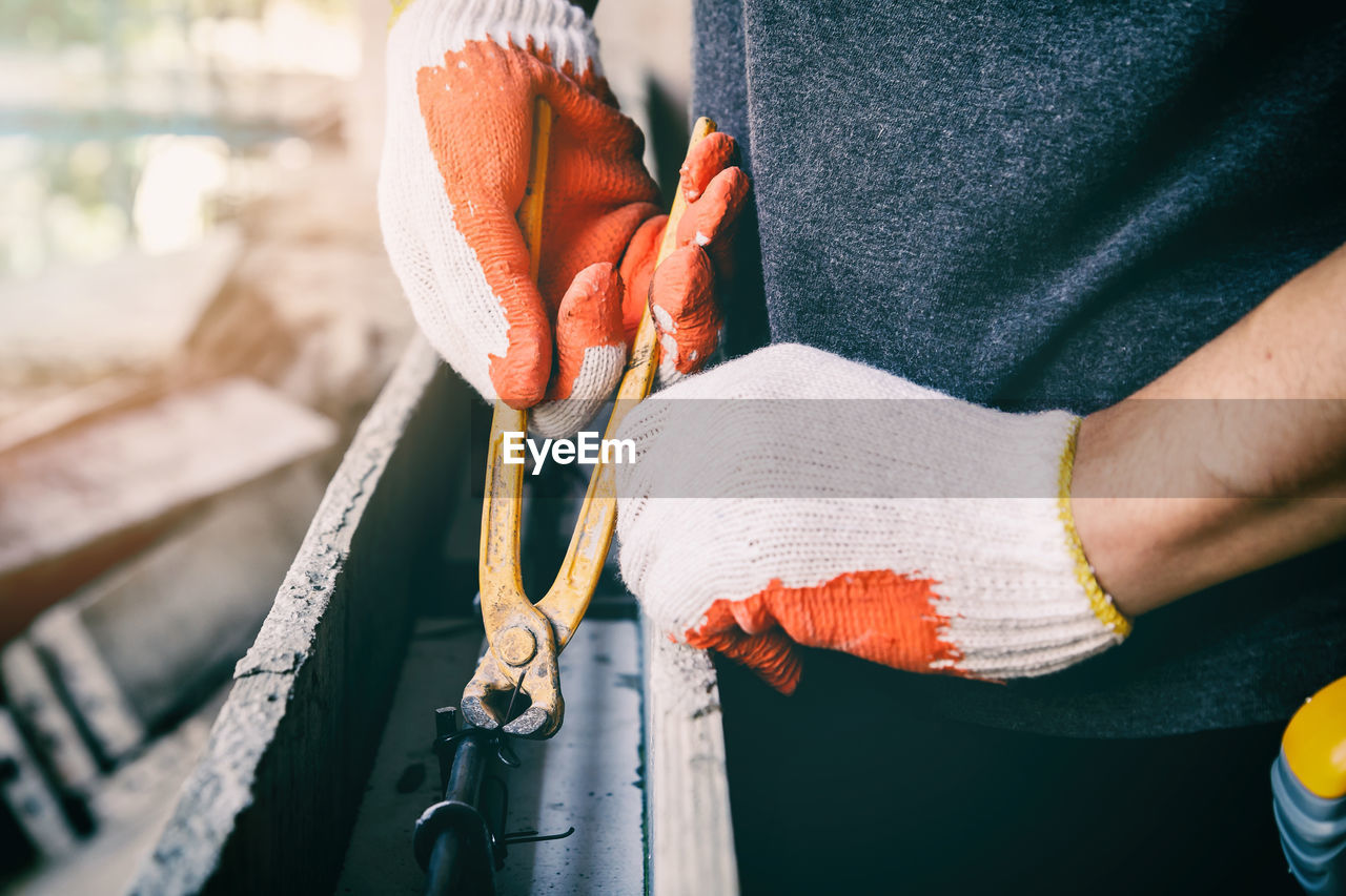 Midsection of man working on metal with pliers