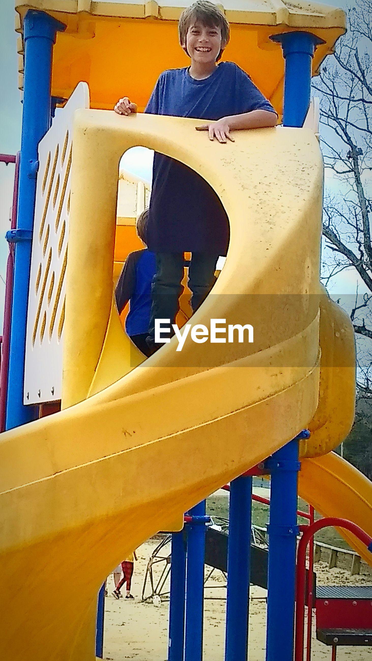 Portrait of boy on slide in playground