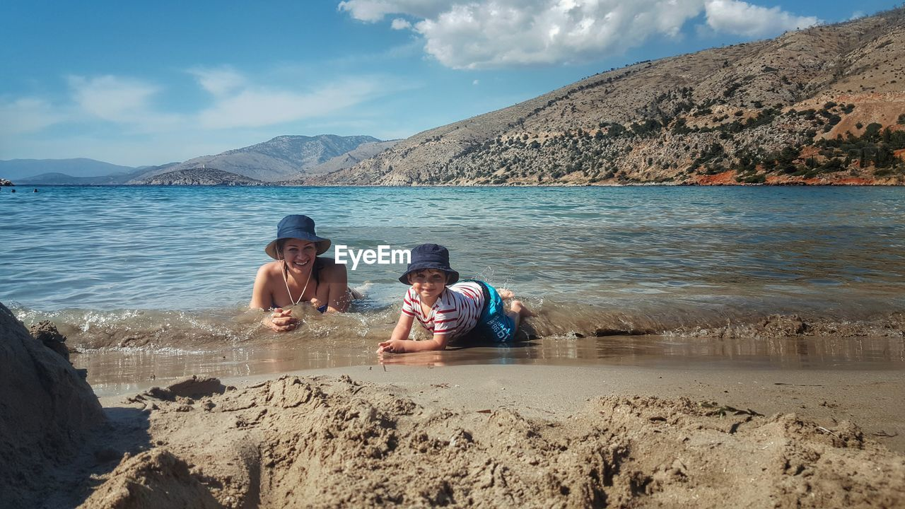 Portrait Of Mother And Son Lying On Shore