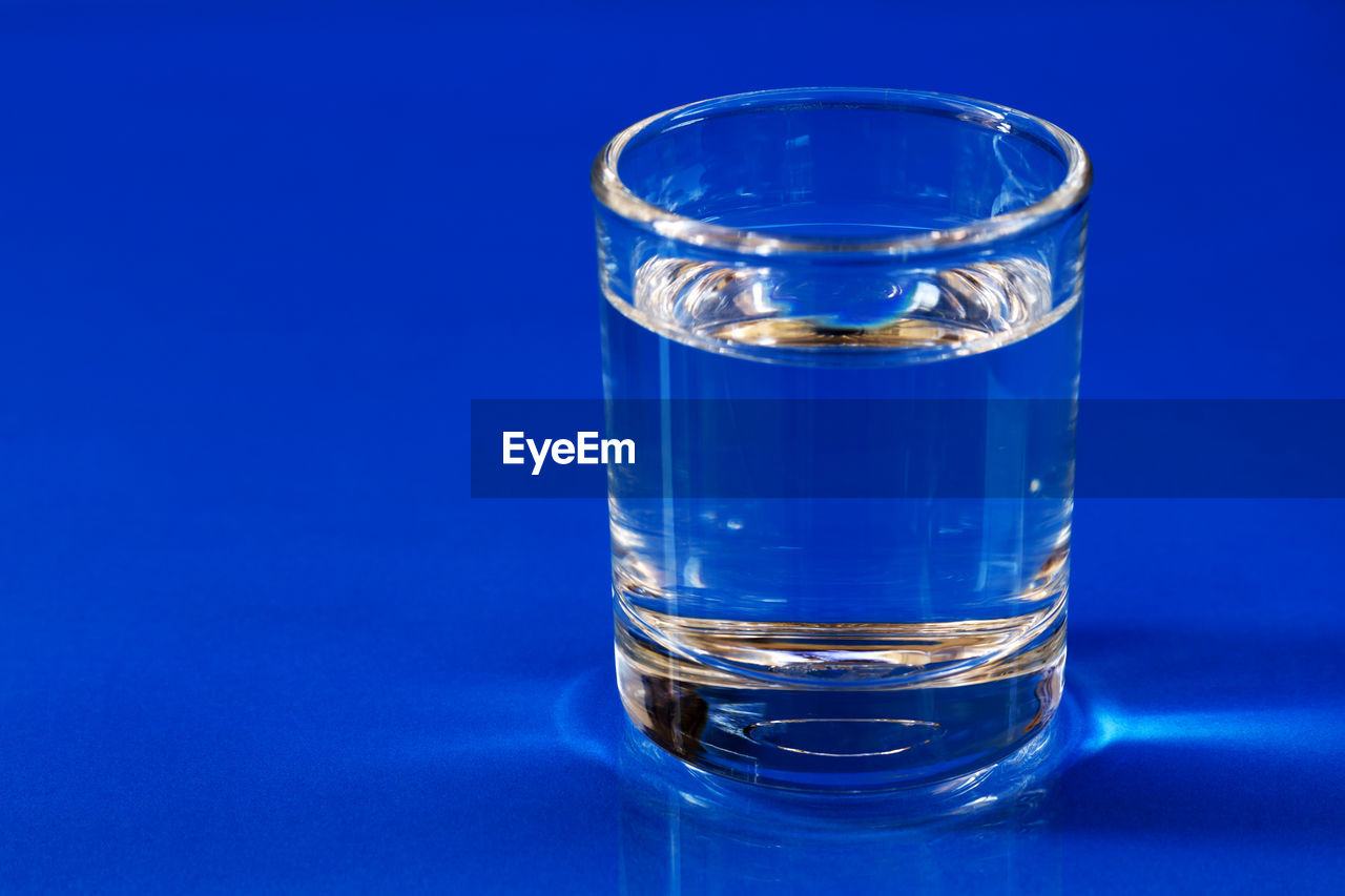 Close-Up Of Water In Glass On Blue Table