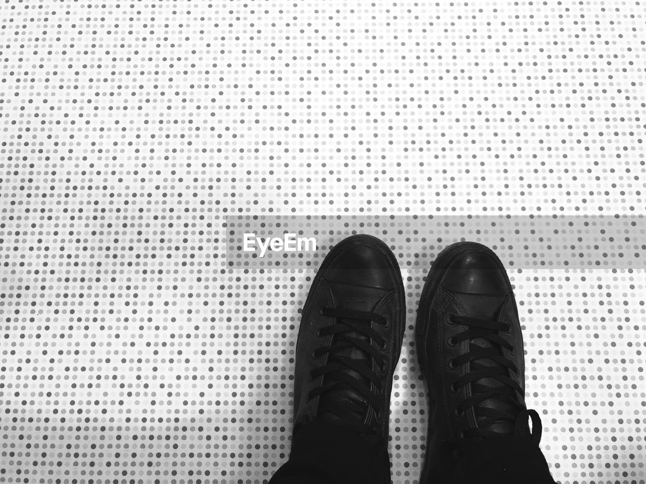 shoe, one person, body part, human body part, standing, low section, human foot, white color, black color, human leg, indoors, lifestyles, men, pair, pattern, clothing, leisure activity, personal perspective, real people, flooring, leather, dress shoe