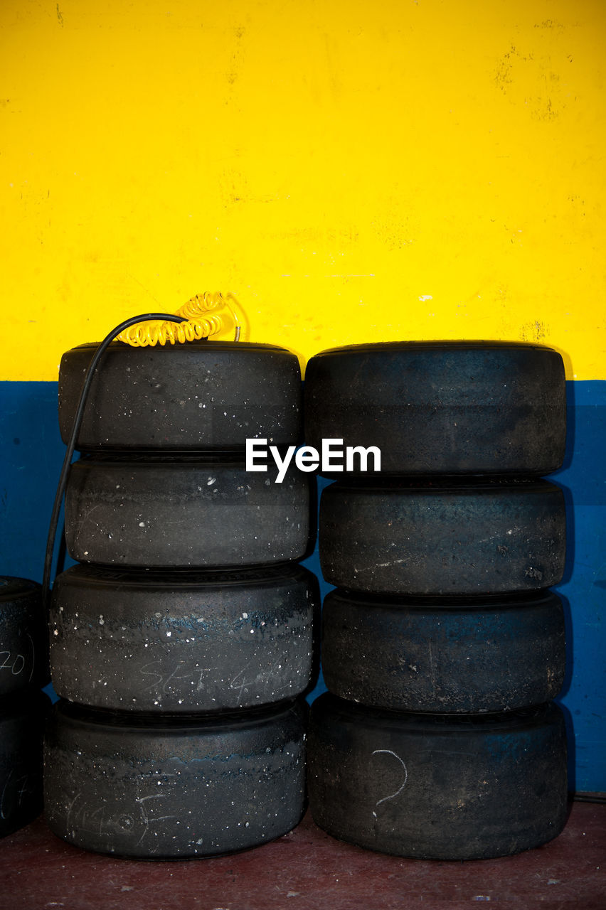 Stacked Tires By Yellow Wall