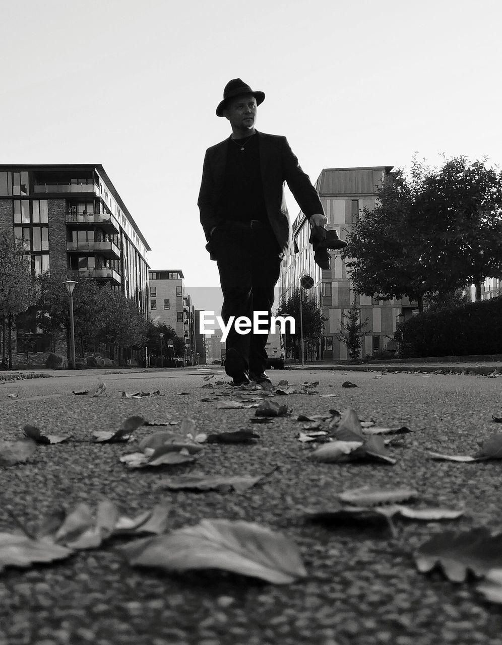 Man walking on street in city against sky