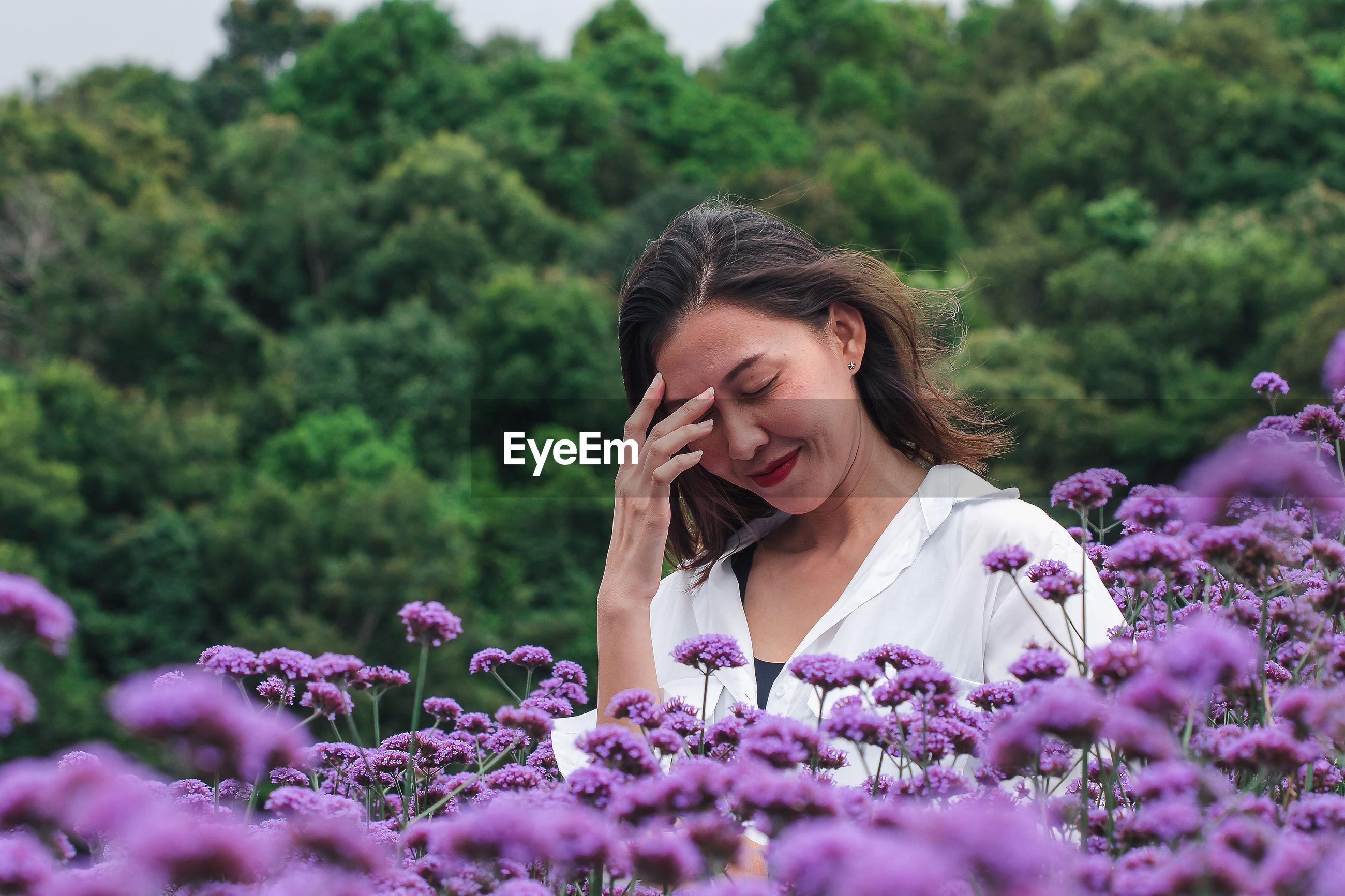 Smiling beautiful woman standing by purple flowering plants