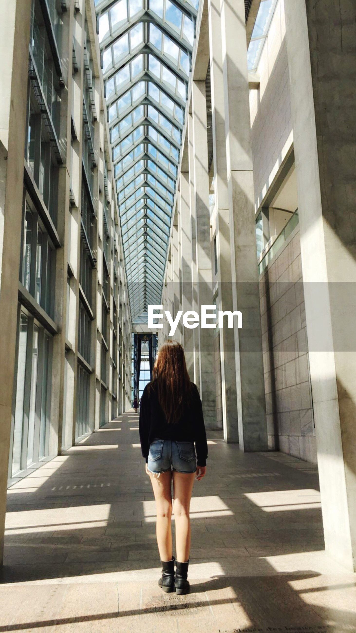 architecture, built structure, full length, lifestyles, casual clothing, building exterior, office building, young adult, day, the way forward, modern, tall - high, outdoors, person, financial district, city life, leading, diminishing perspective