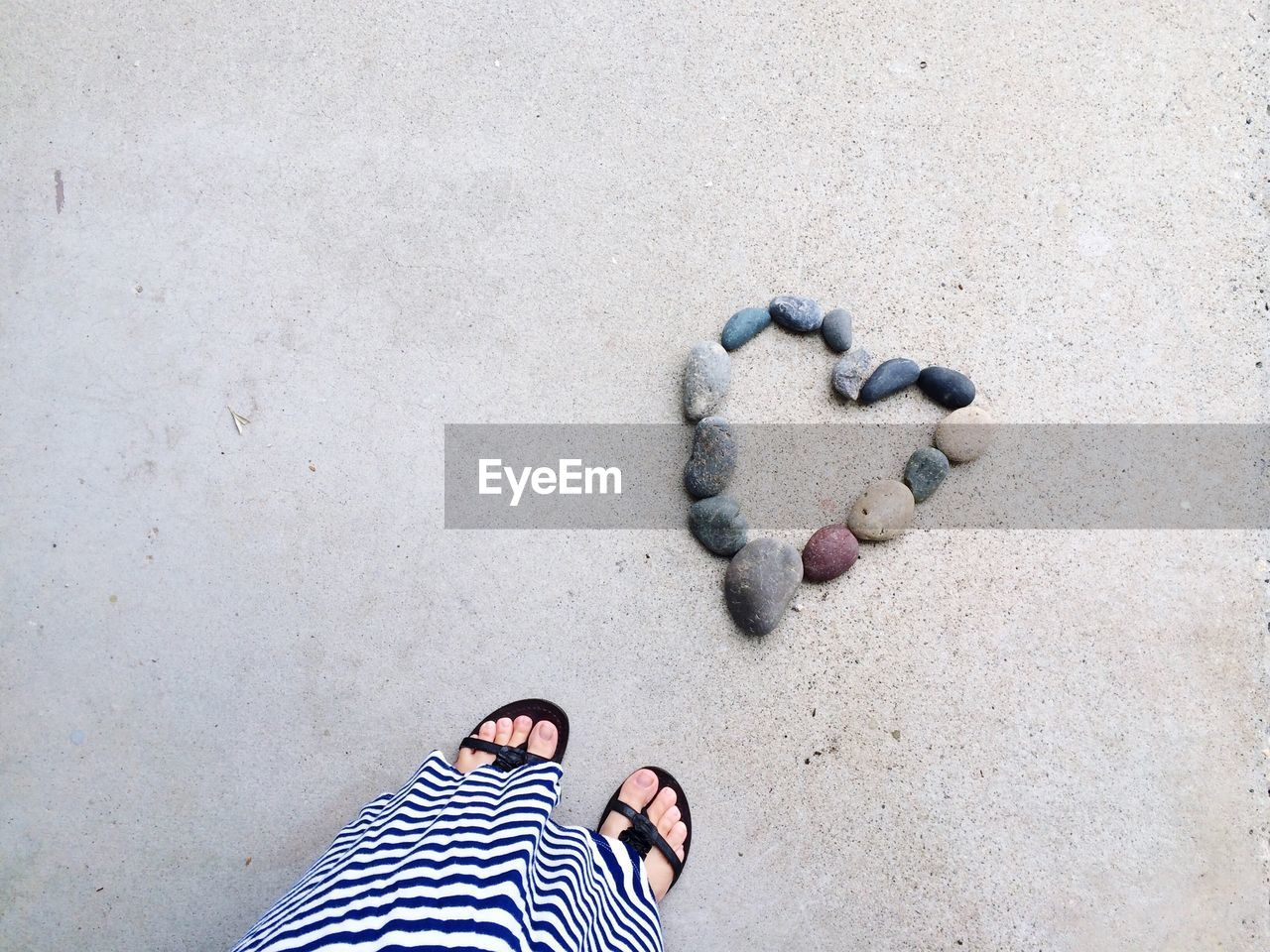 Low Section Of Woman With Heart Shape Pebbles At Beach