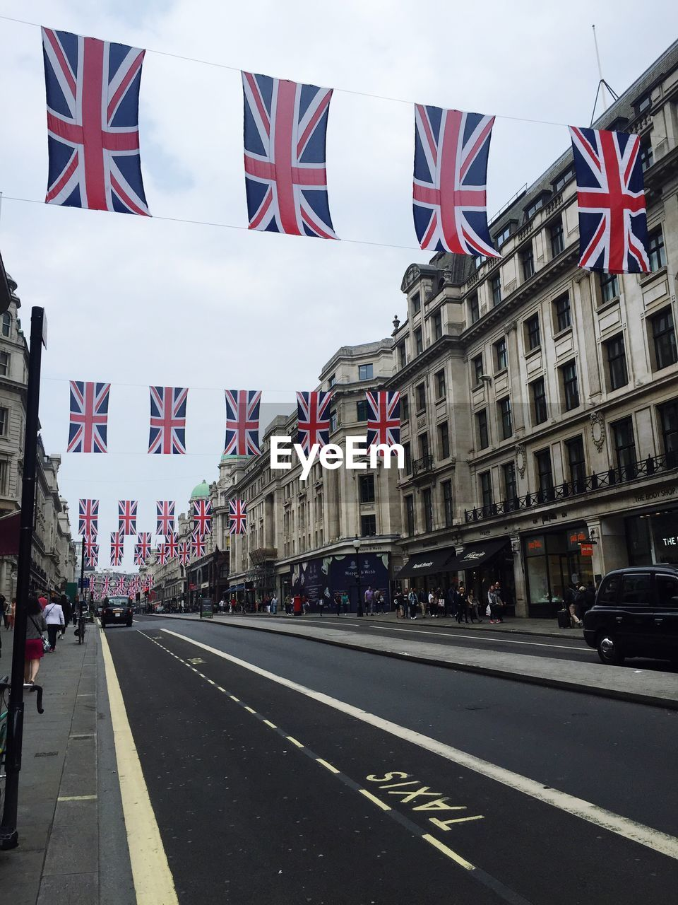 British Flags Handing Over Road Against Cloudy Sky