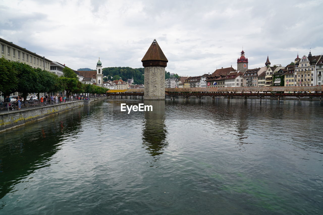 architecture, built structure, building exterior, water, sky, building, cloud - sky, river, city, waterfront, nature, bridge, connection, travel destinations, day, bridge - man made structure, group of people, incidental people, travel, outdoors