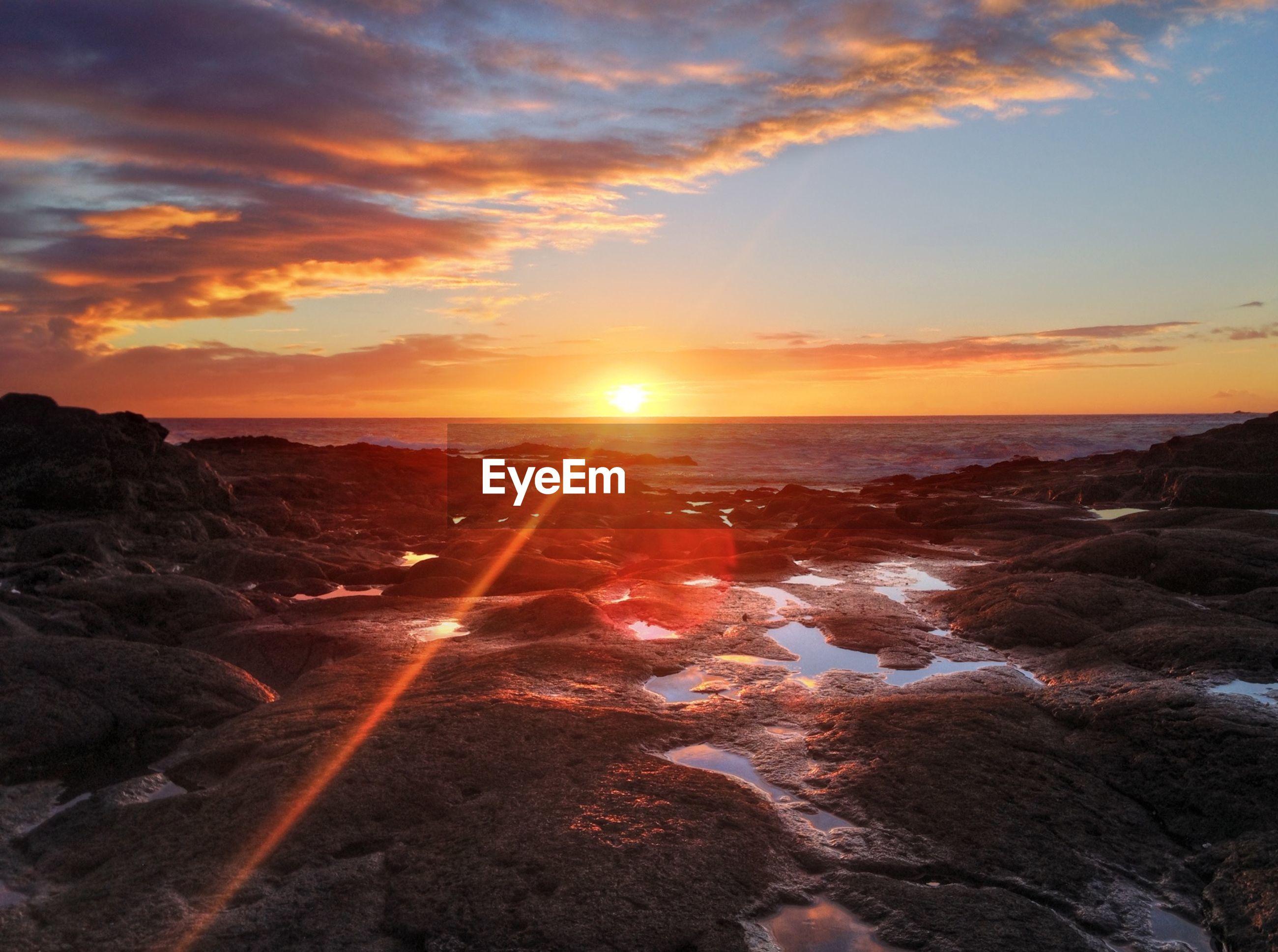 sunset, sun, sea, sky, water, scenics, beauty in nature, beach, tranquil scene, orange color, tranquility, horizon over water, cloud - sky, sunbeam, nature, shore, lens flare, sunlight, idyllic, rock - object