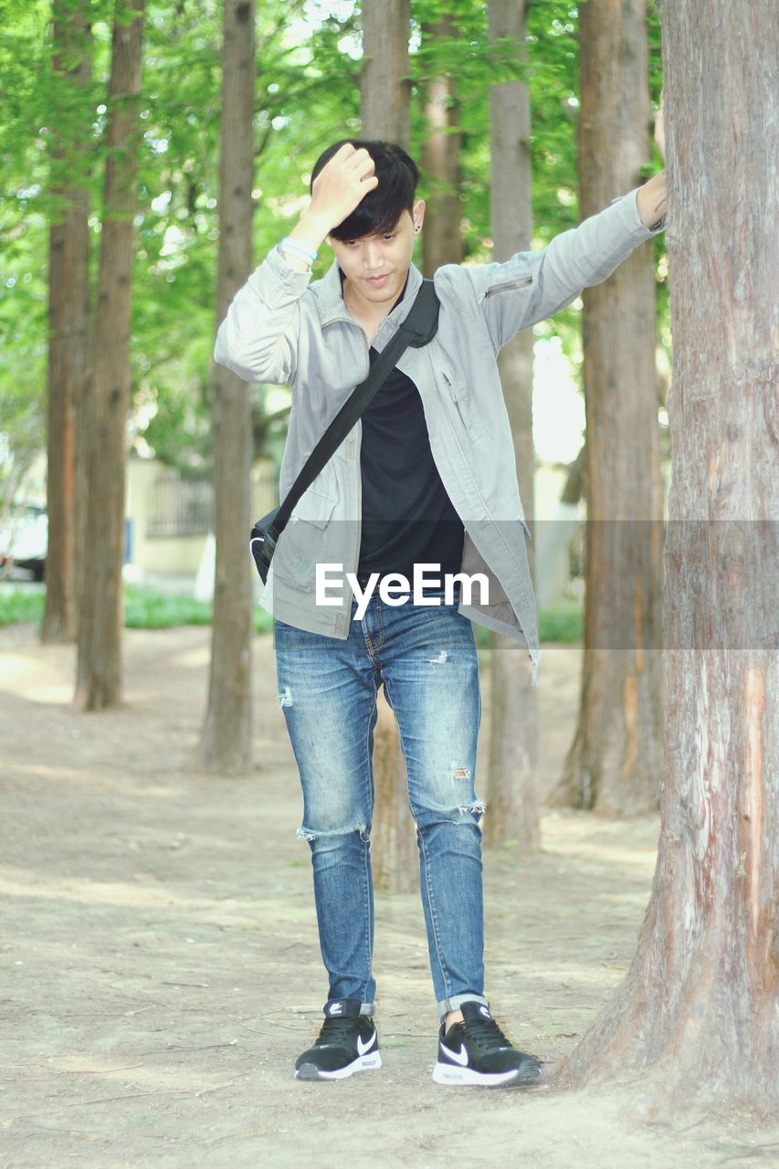 casual clothing, jeans, one person, front view, full length, tree, young men, tree trunk, lifestyles, young adult, real people, smiling, standing, day, leisure activity, outdoors, forest, portrait, happiness, looking at camera, nature, one man only, men, only men, adults only, adult, people