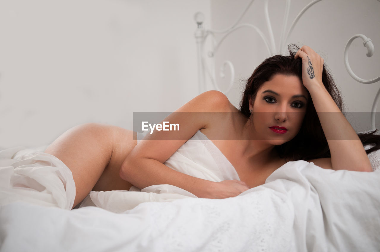 Portrait of seductive young woman lying on bed at home