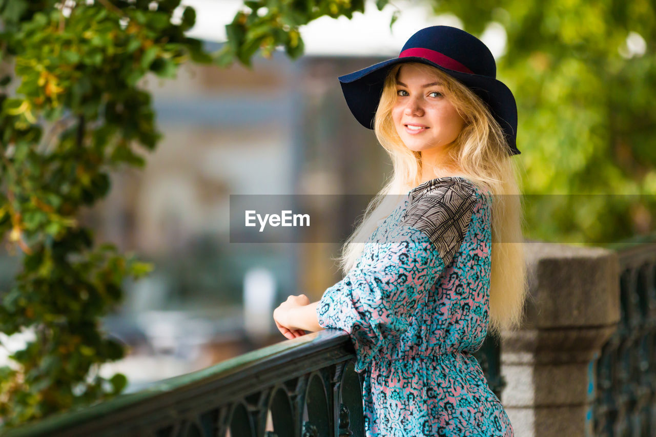 one person, real people, hat, leisure activity, young adult, looking at camera, portrait, young women, clothing, lifestyles, hair, focus on foreground, casual clothing, women, blond hair, standing, smiling, hairstyle, side view, beautiful woman, fashion, outdoors