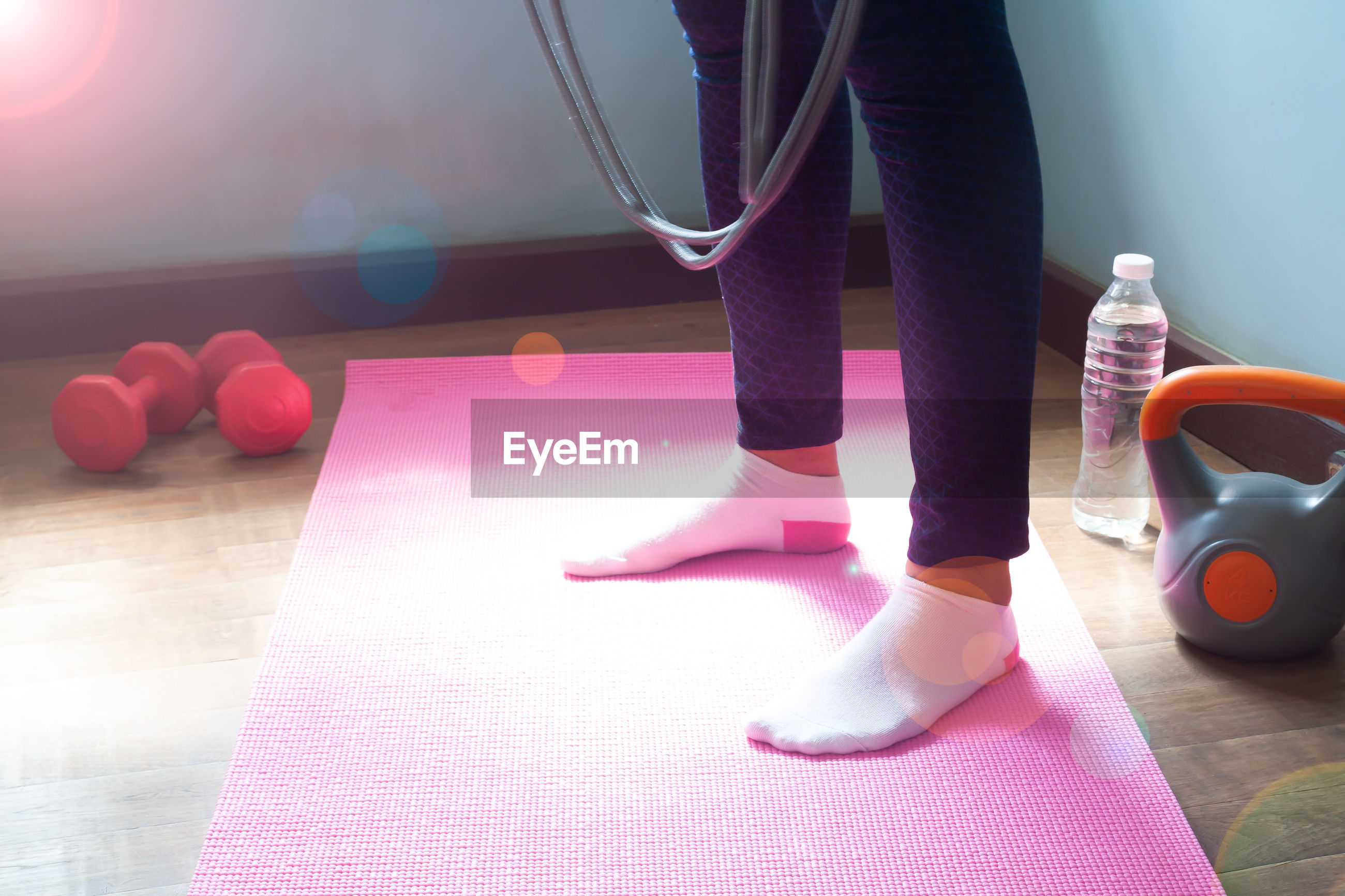 Low section of woman standing on exercise mat at home during sunny day
