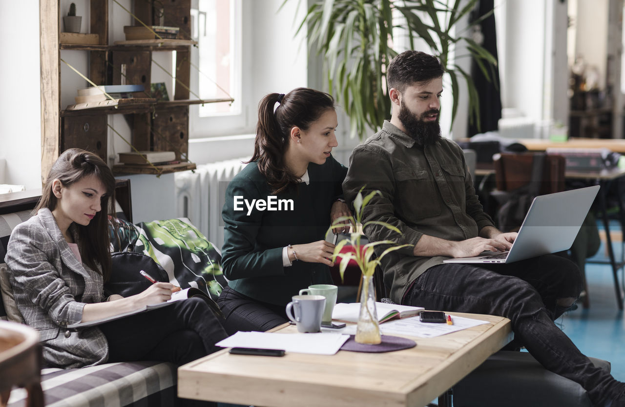 Business People Working While Sitting By Table