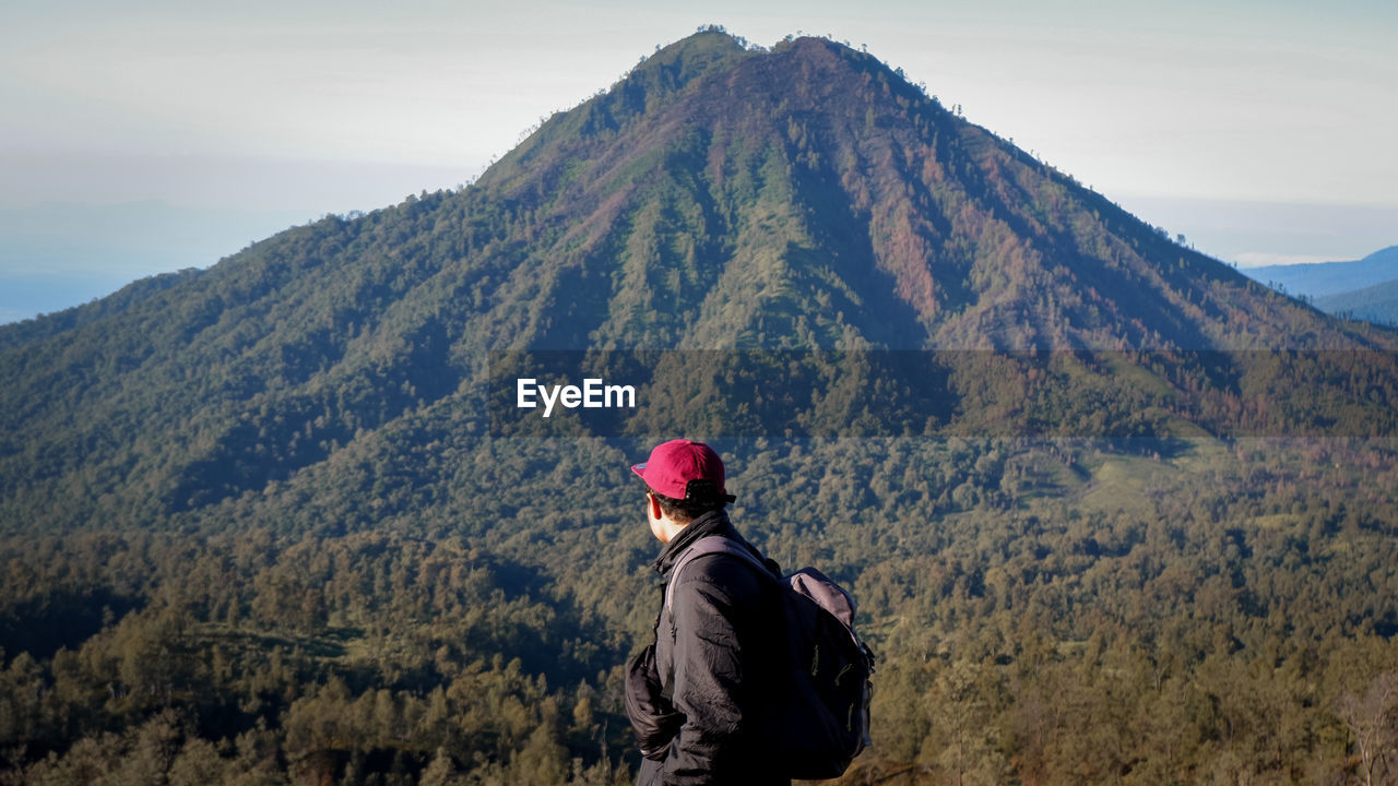 Side view of young man looking at mountain against sky