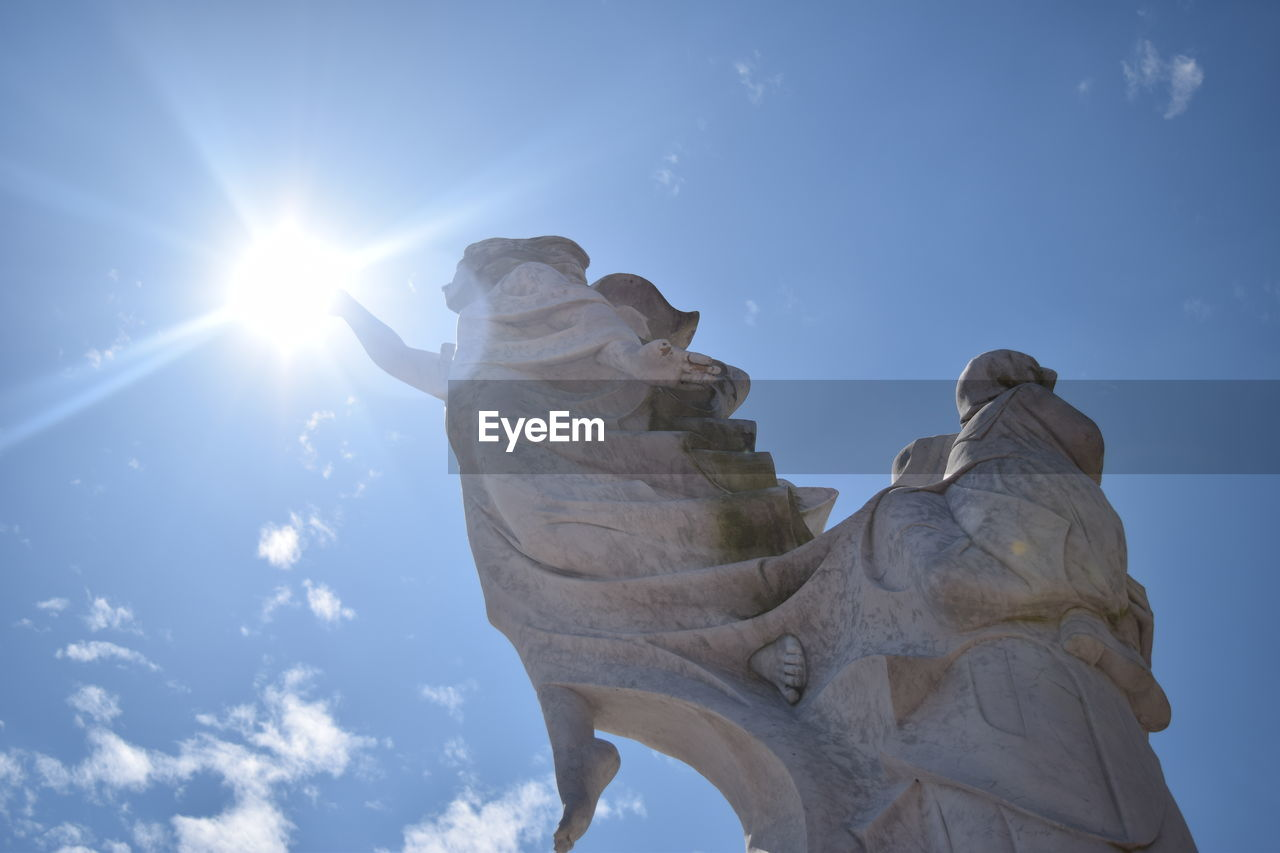 low angle view, sculpture, sky, representation, statue, art and craft, human representation, sunlight, creativity, nature, lens flare, architecture, no people, craft, sunbeam, day, belief, cloud - sky, sun, religion, outdoors, angel