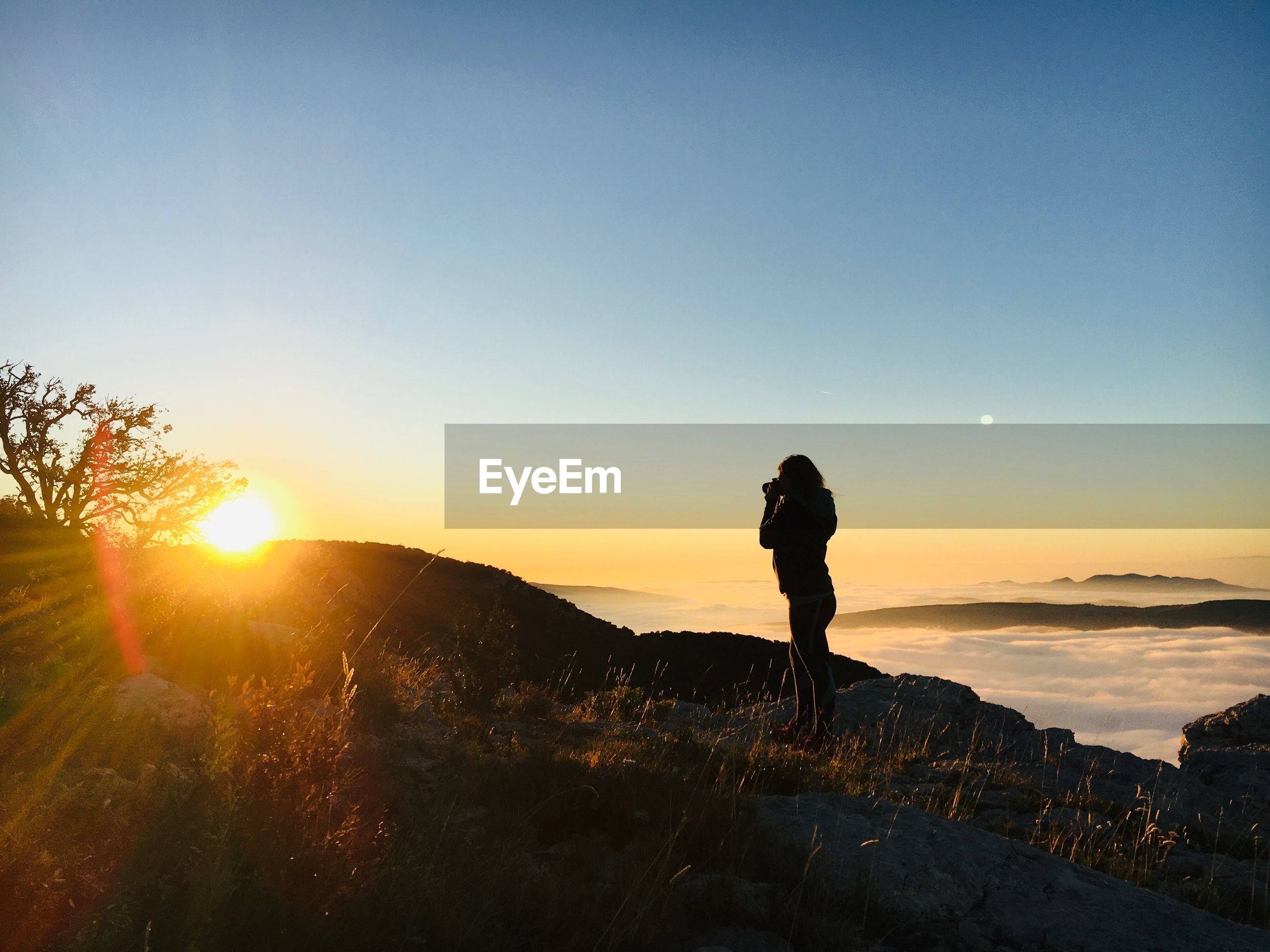 Silhouette woman standing on mountain against sky during sunset