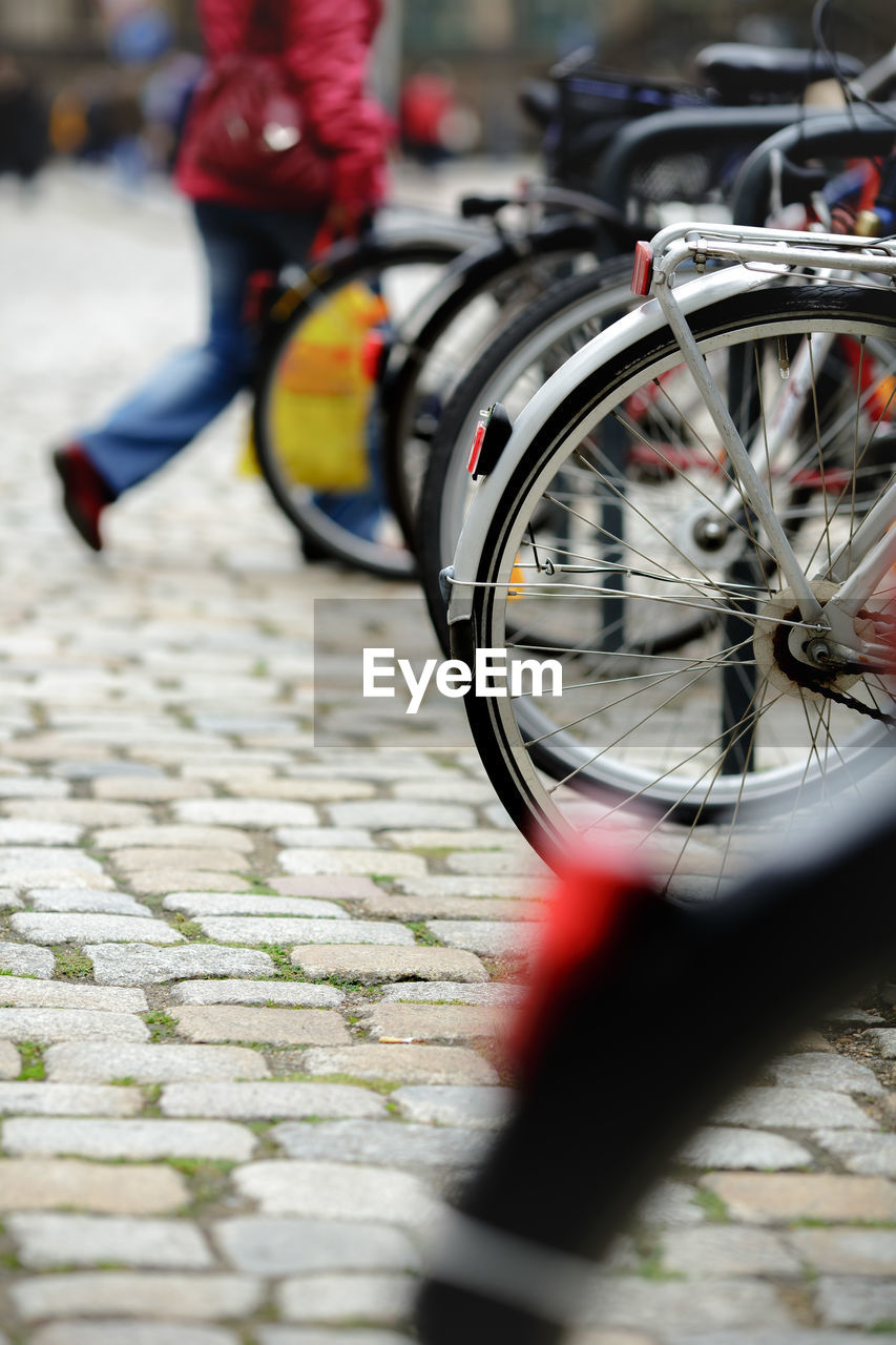 bicycle, transportation, mode of transportation, selective focus, land vehicle, street, city, wheel, day, low section, real people, footpath, lifestyles, people, outdoors, incidental people, focus on foreground, red, human leg, tire, spoke, paving stone