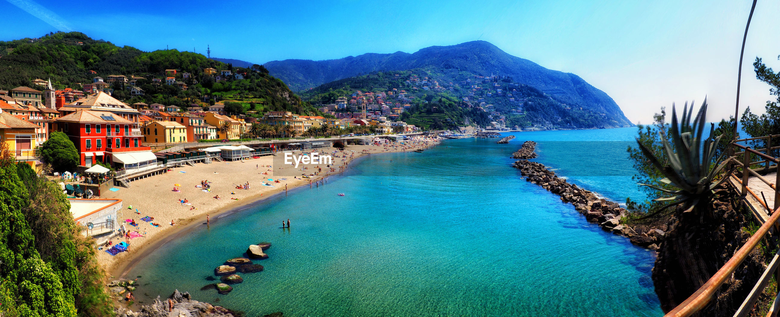 PANORAMIC VIEW OF SEA AND MOUNTAINS AGAINST BLUE SKY