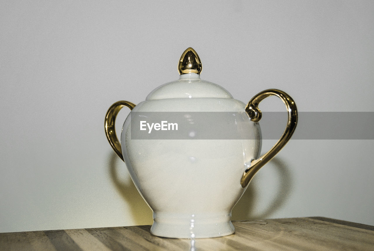 still life, single object, no people, indoors, table, teapot, close-up, white background, day