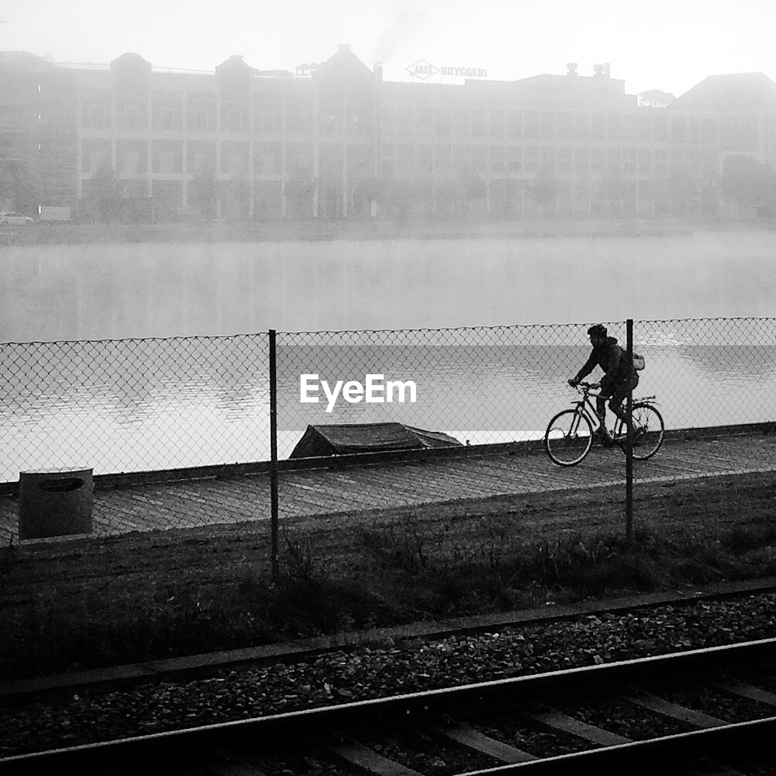 Young man cycling by river