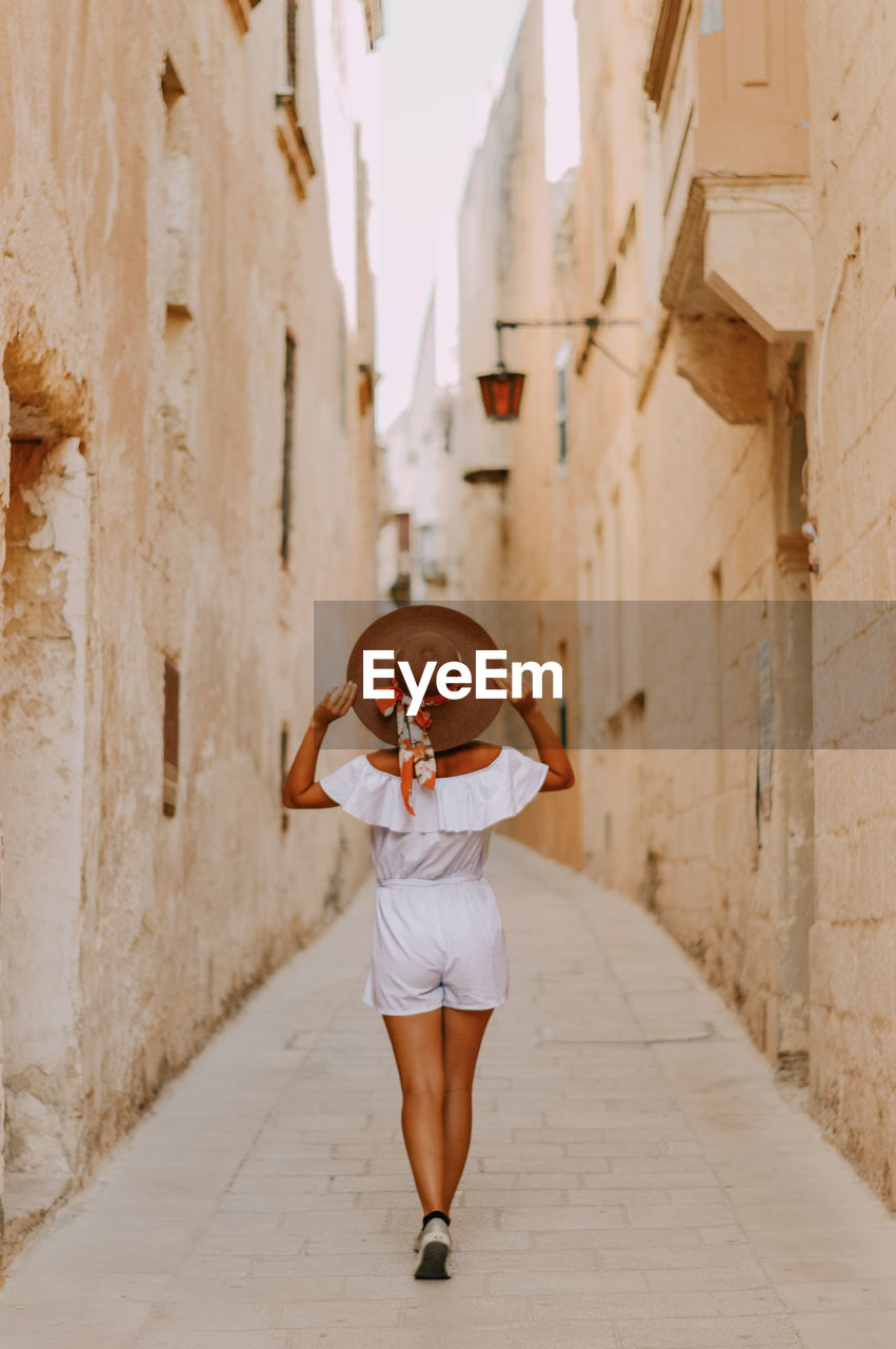Full length of woman standing amidst buildings in silent city mdina in malta