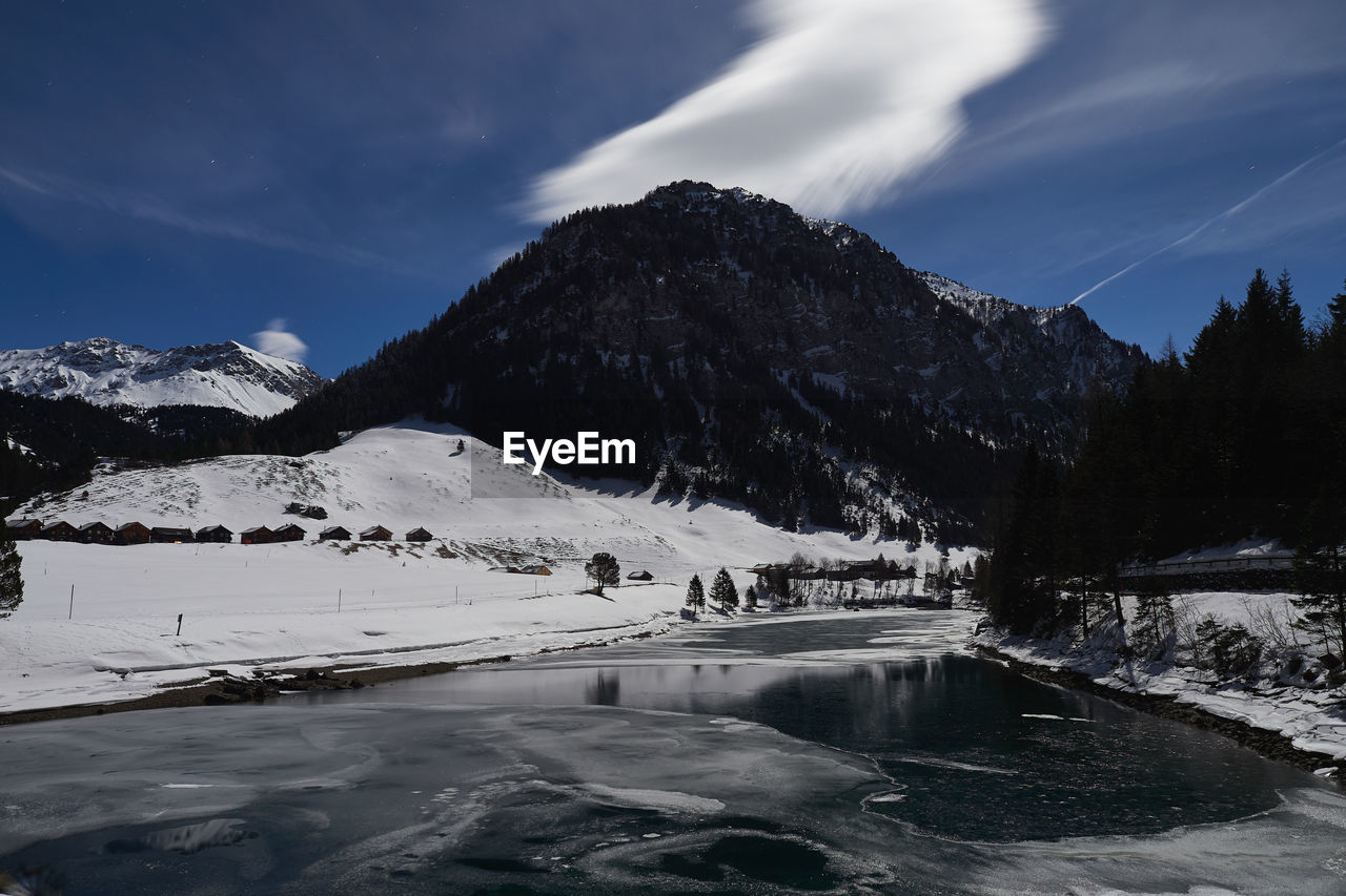 mountain, cold temperature, water, sky, snow, winter, nature, scenics - nature, beauty in nature, tree, lake, environment, transportation, day, cloud - sky, outdoors, winter sport, waterfront, snowcapped mountain