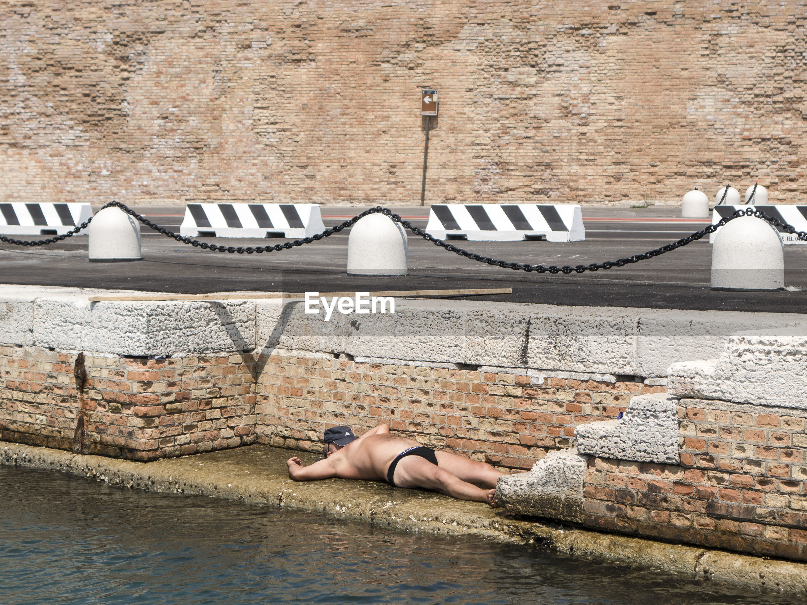 one person, lying down, real people, day, architecture, relaxation, full length, lifestyles, water, leisure activity, adult, built structure, nature, young adult, wall, women, resting, high angle view, building exterior, outdoors, stone wall