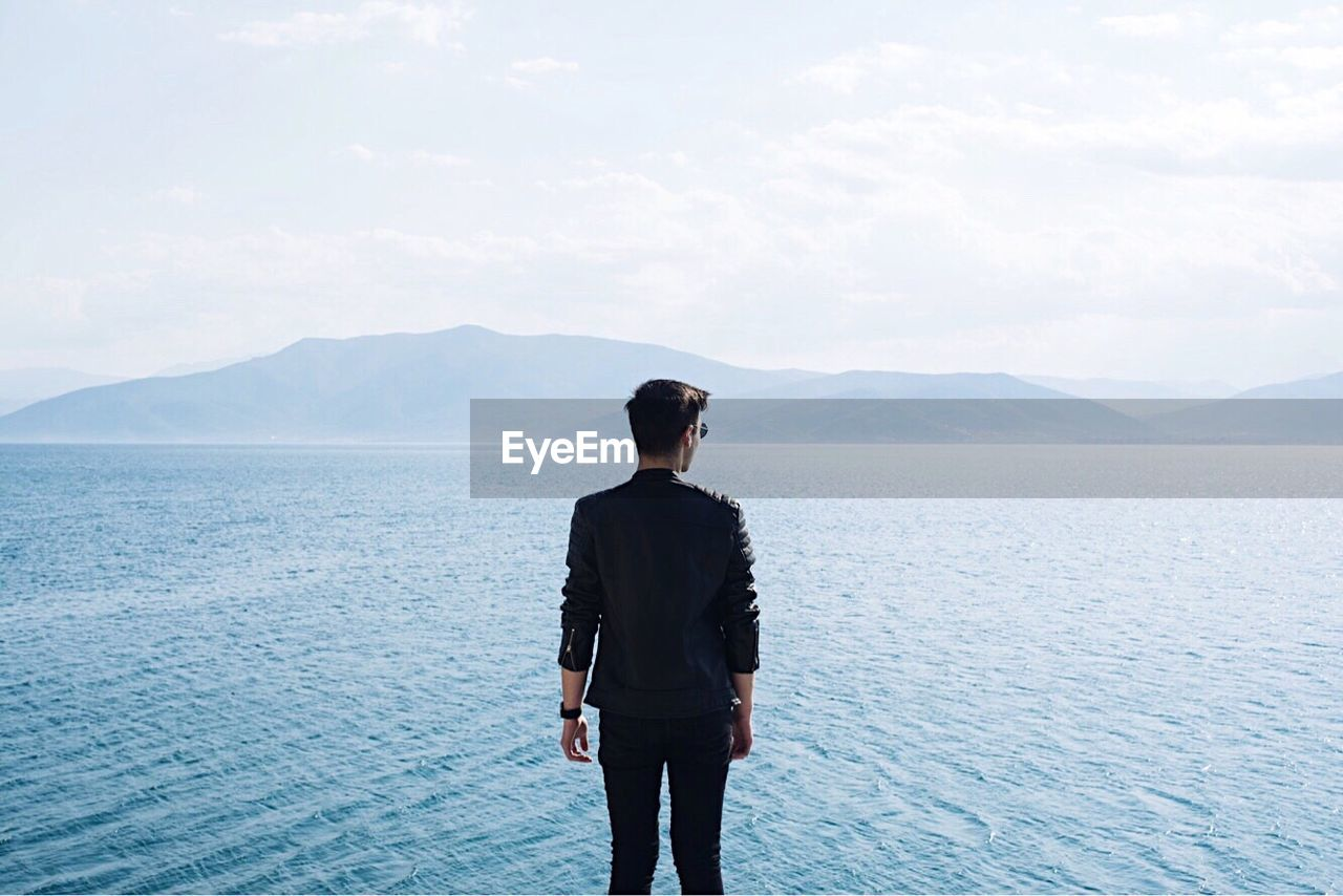 Young Man Standing In Front Of Sea