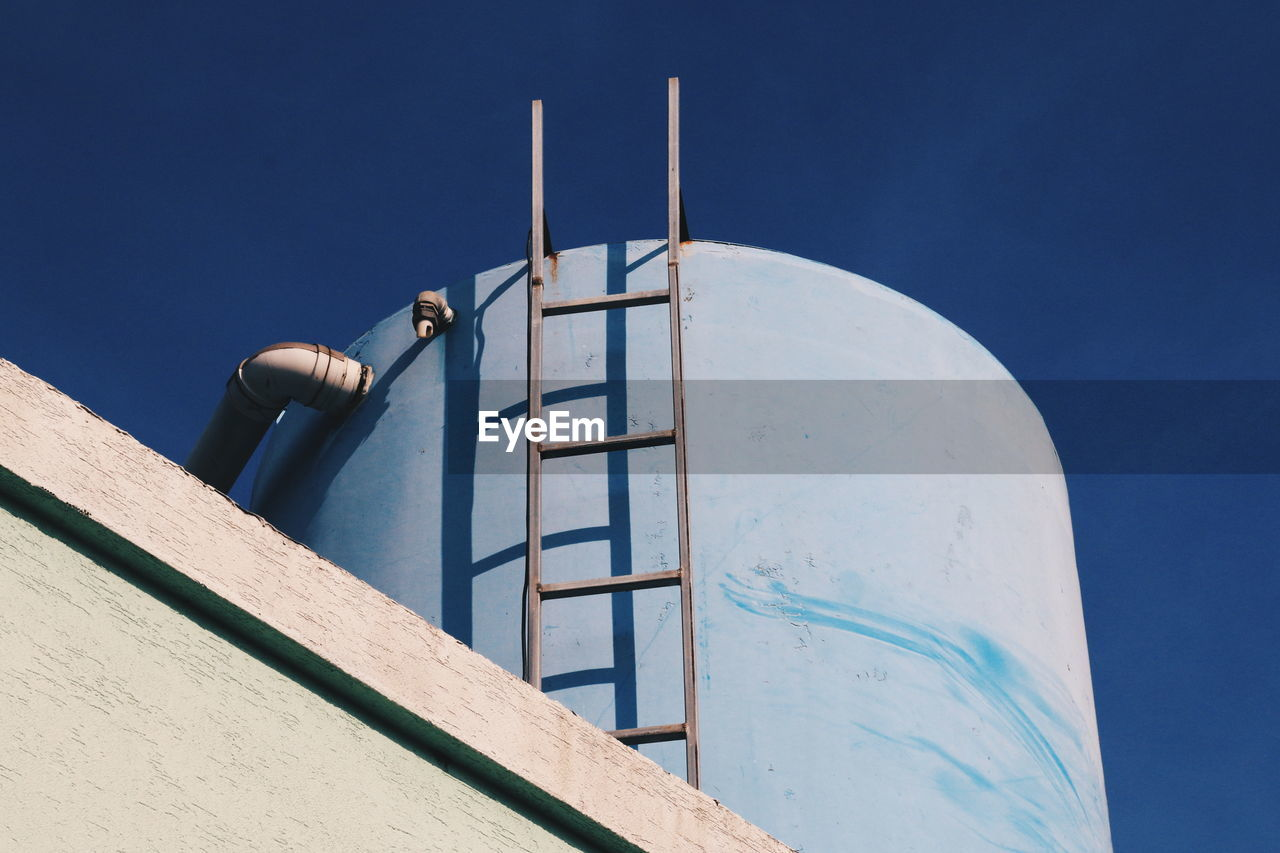 Low angle view of water storage tank against blue sky