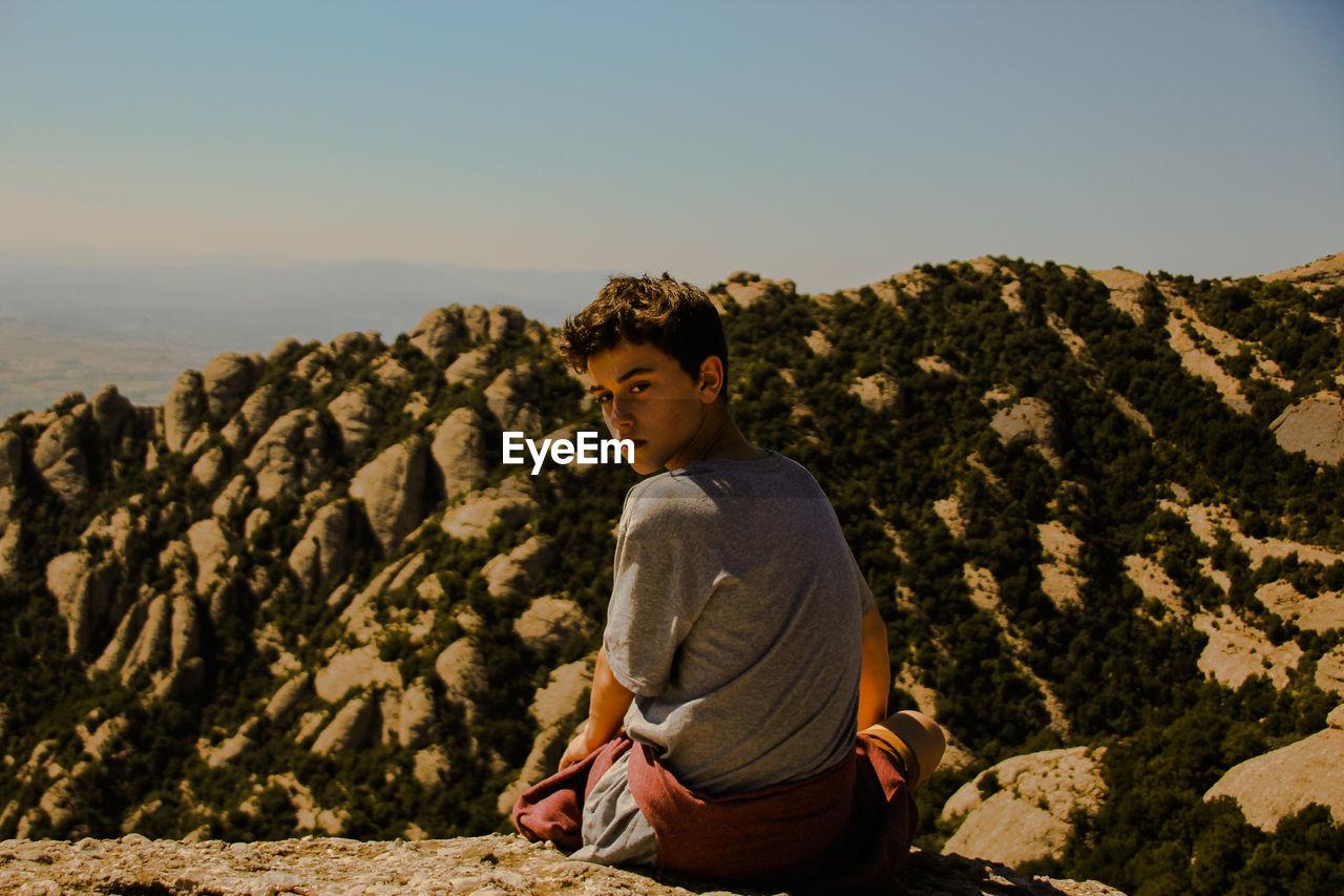 Boy Sitting On Rock Against Clear Sky