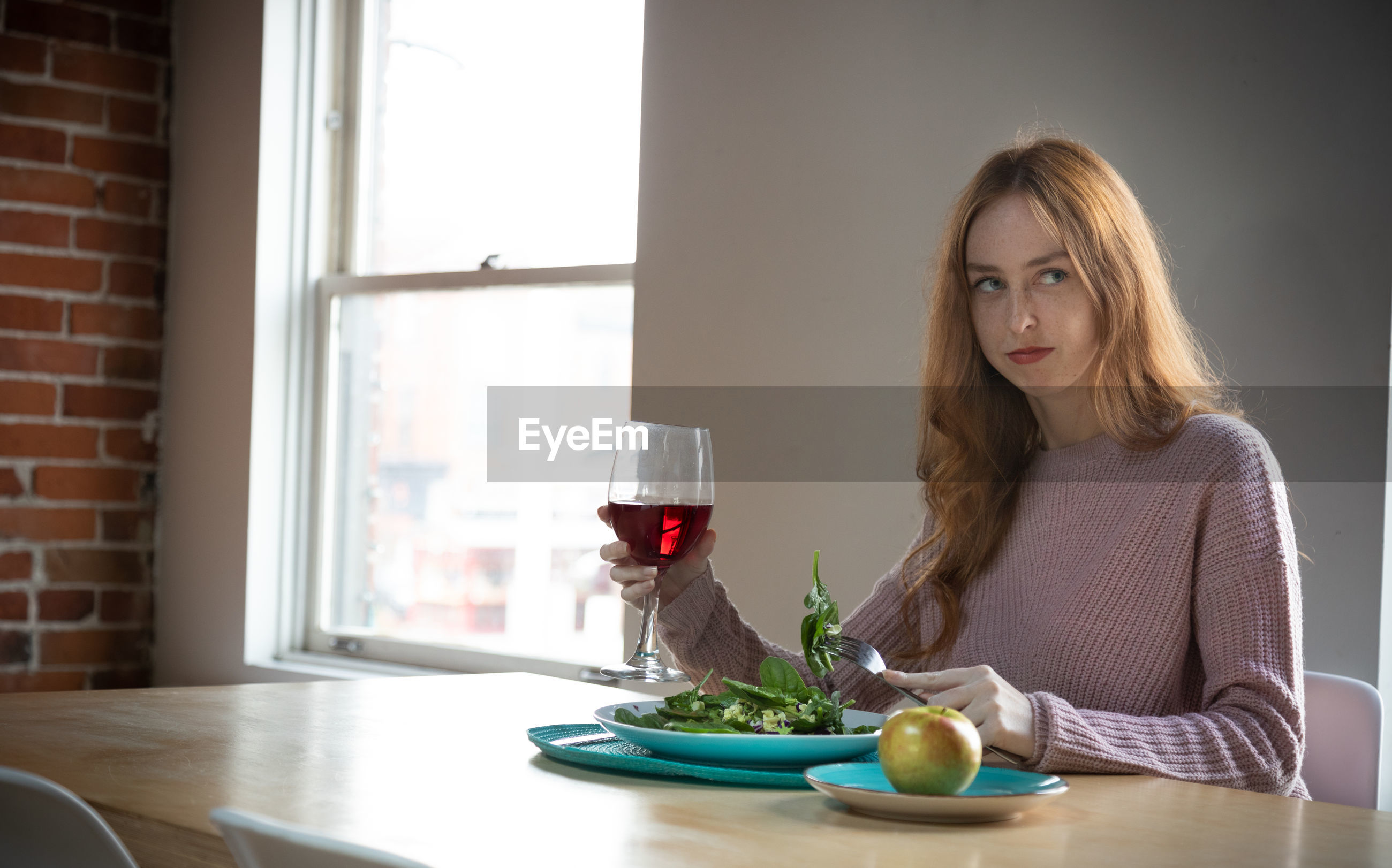 Young woman looking away while having salad and red wine at home