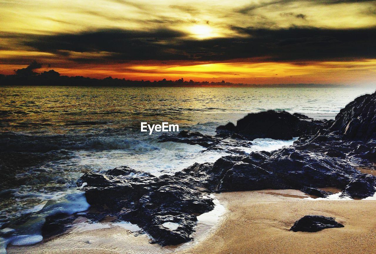 Rocks on sea shore during sunset