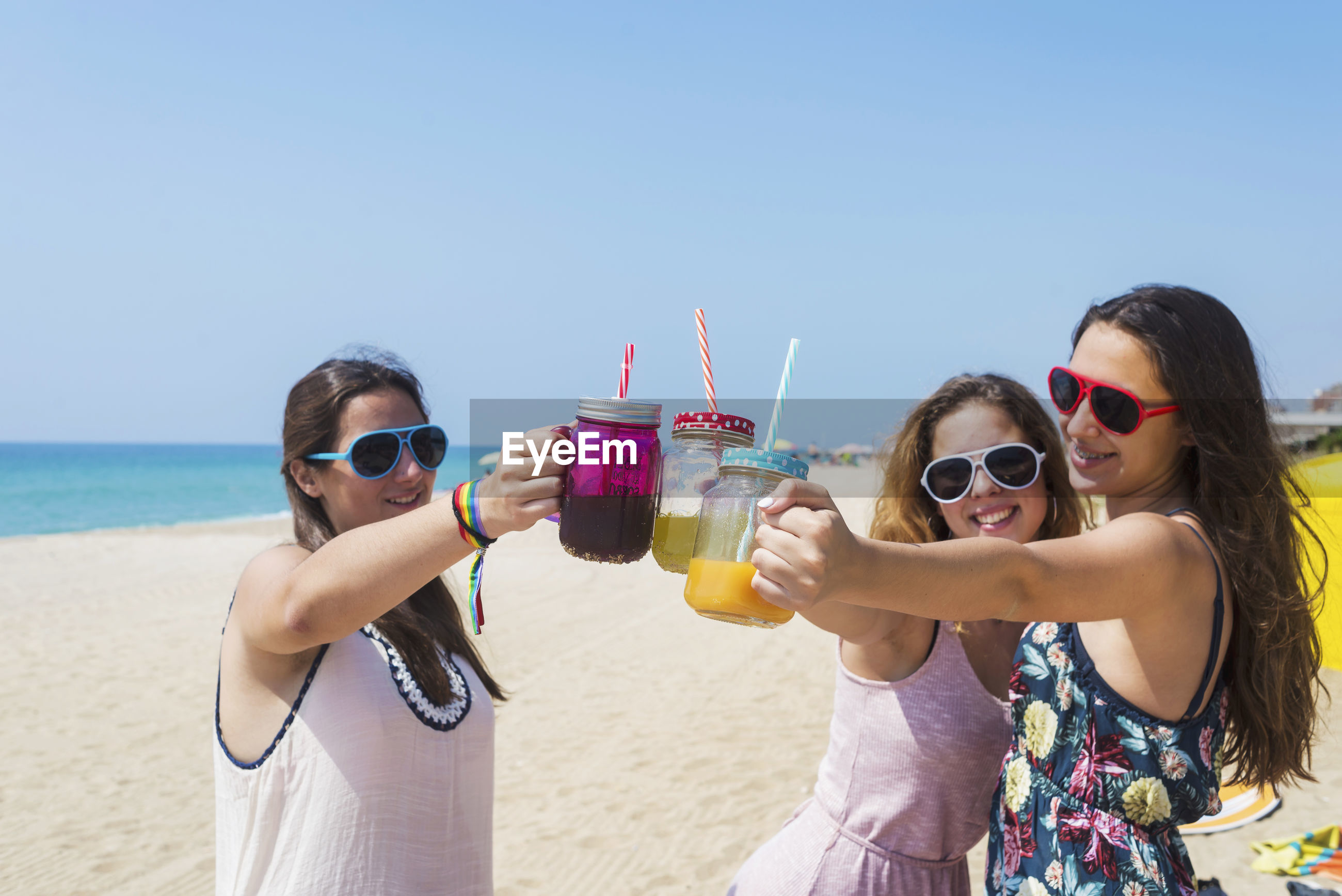 Smiling woman and girls toasting while holding juice in glasses at beach against sky
