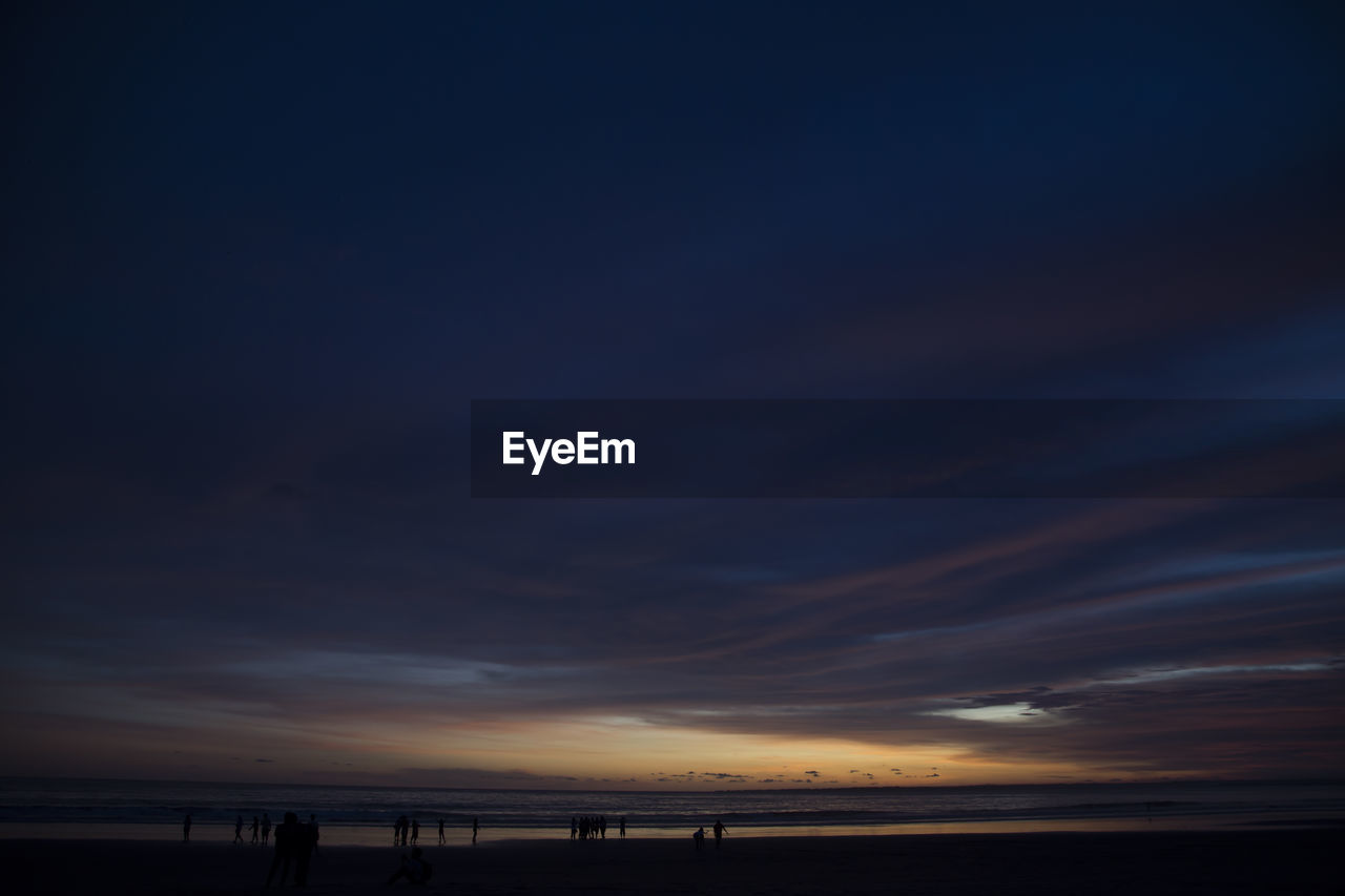 Scenic view of cloudy sky over beach at sunset
