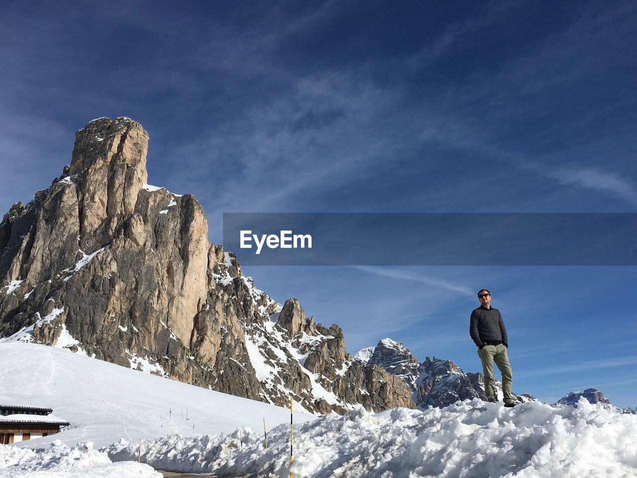Low Angle View Of Man Standing On Snow Covered Mountain Against Sky