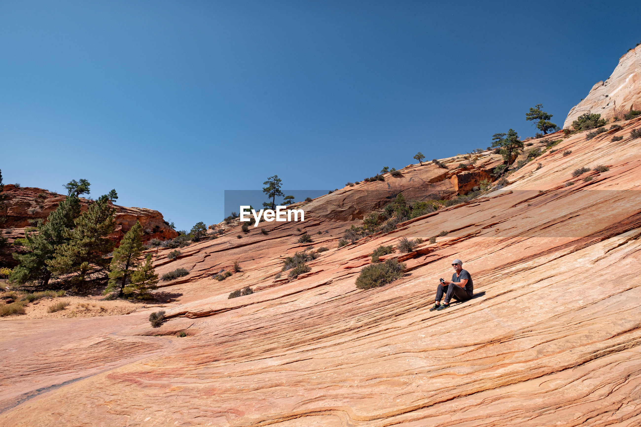 Man on rock mountain against clear blue sky