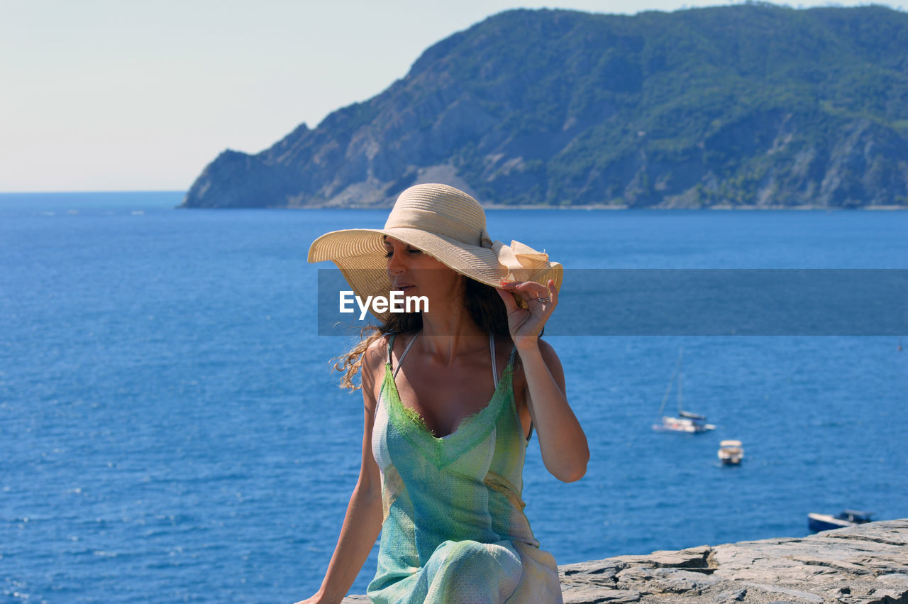 Woman in hat sitting at sea against mountains