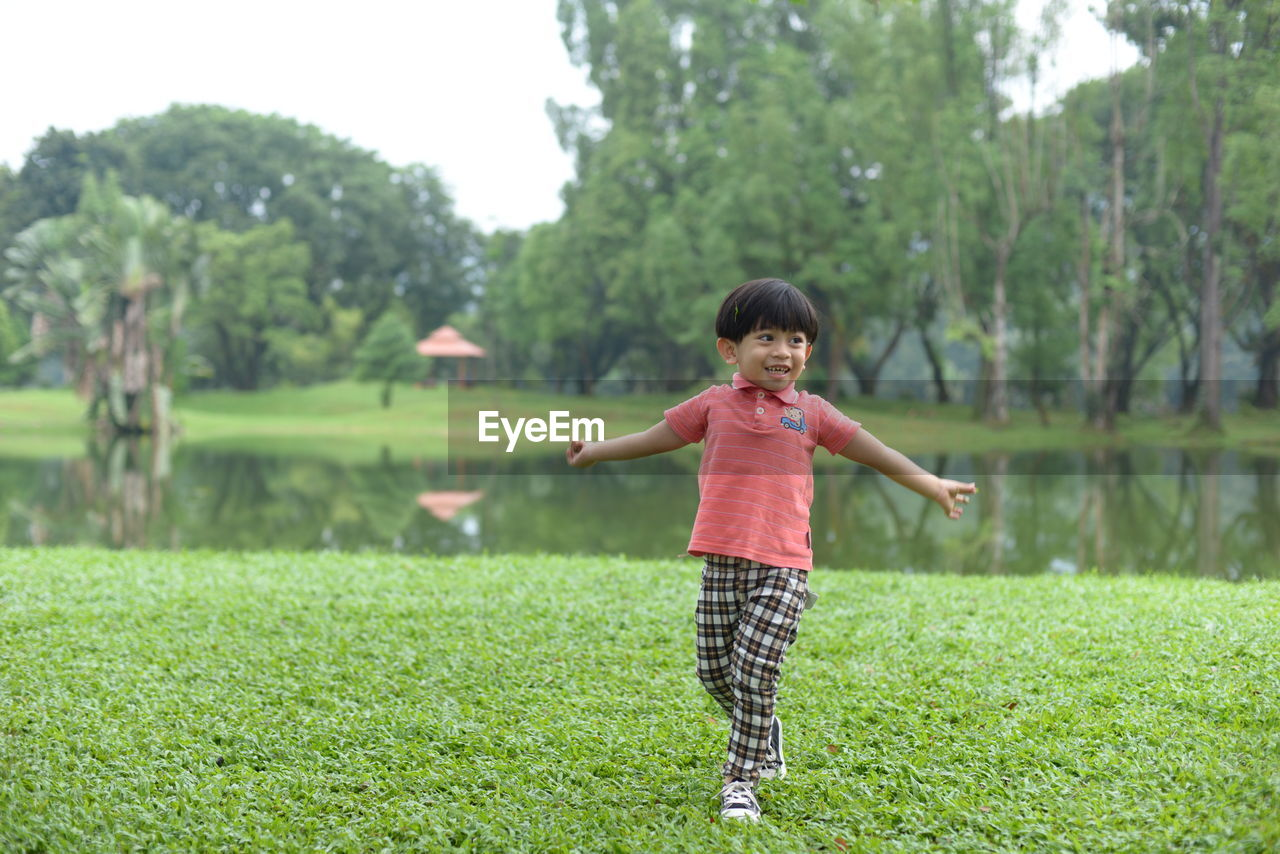 Full length of cheerful boy walking on field at park