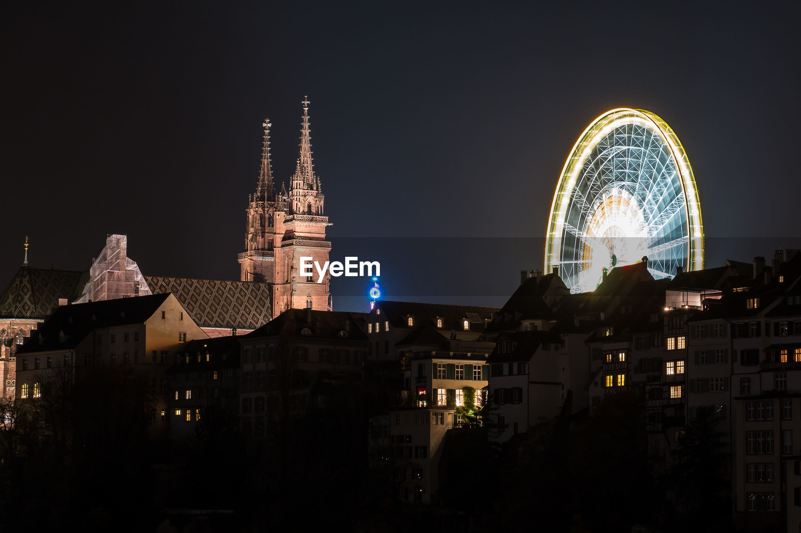 Illuminated wiener riesenrad and church in city against clear sky