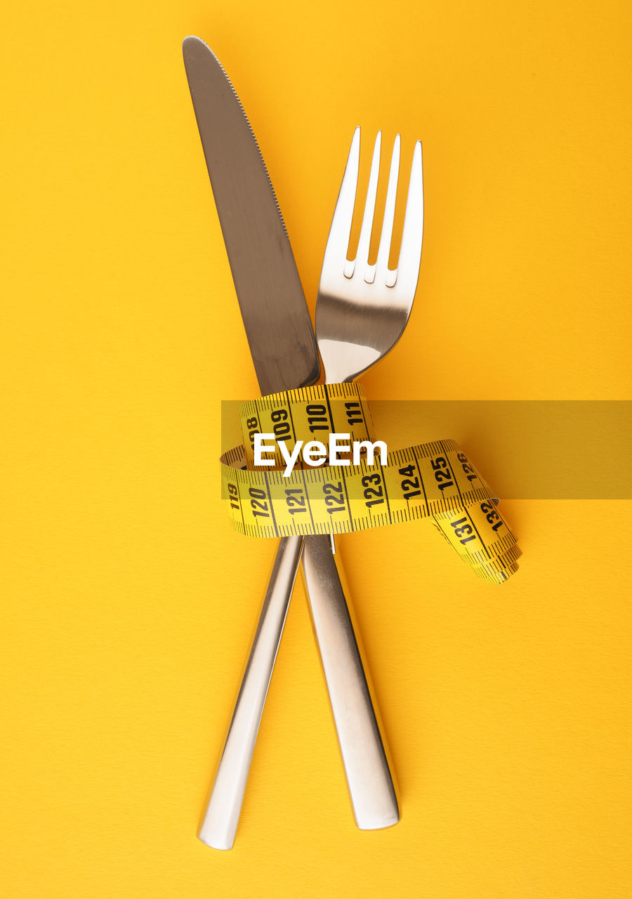 yellow, indoors, still life, no people, close-up, studio shot, high angle view, representation, origami, single object, instrument of measurement, eating utensil, art and craft, text, colored background, yellow background, cut out, pattern, creativity, number