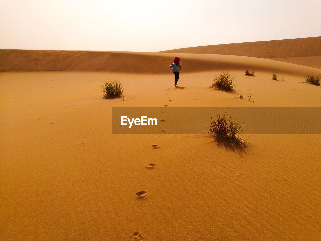 Rear View Of Woman Walking On Desert Against Clear Sky