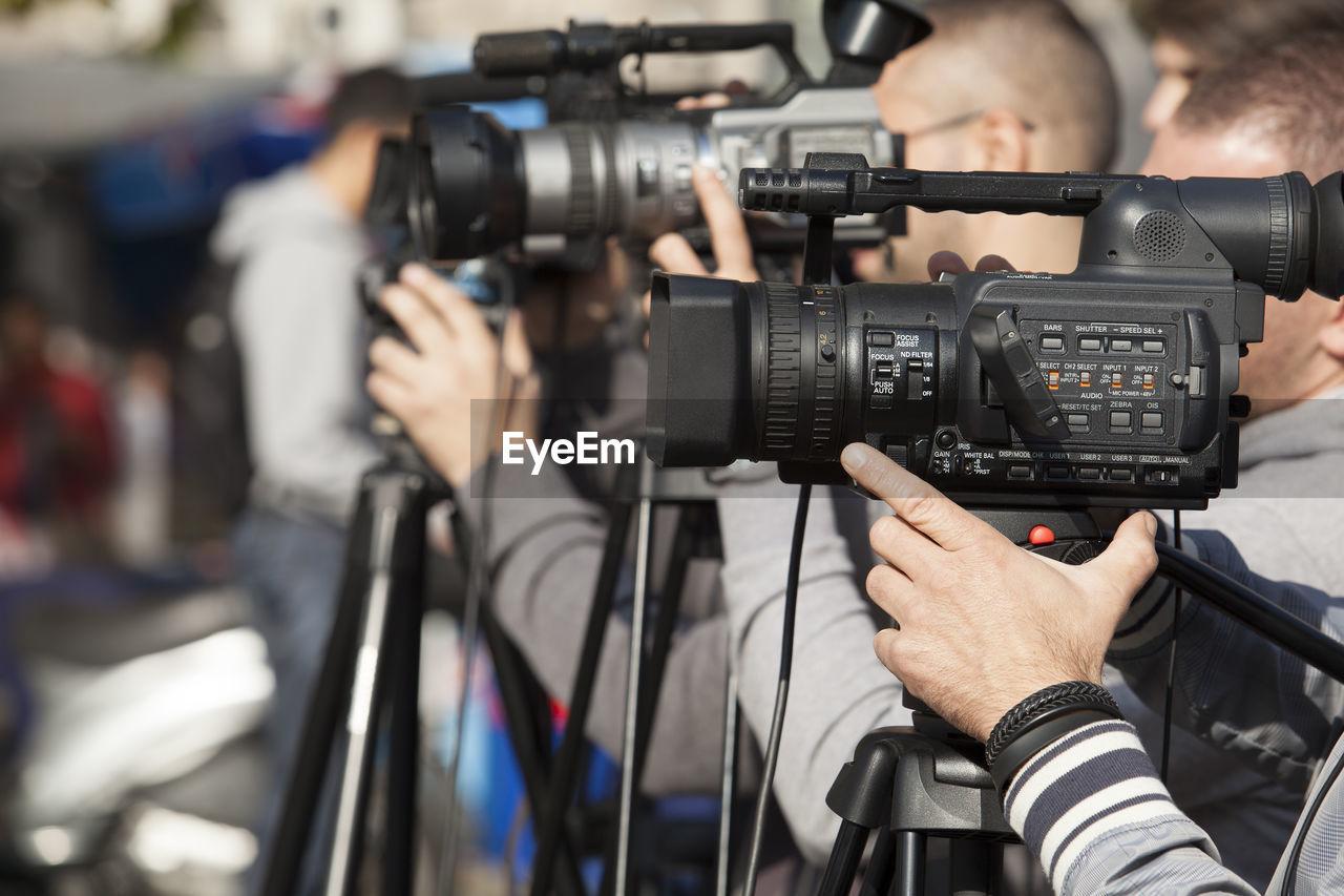 Close-up of men photographing through camera